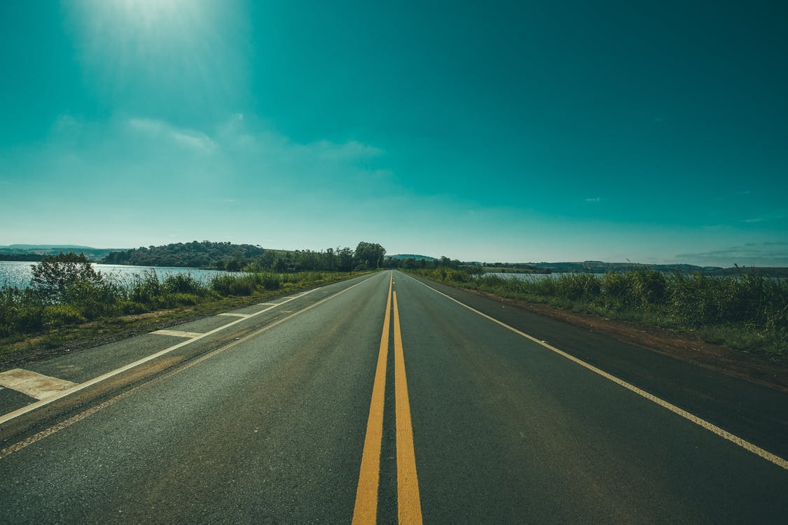 Panoramic Photography of Road Between Grasses and Body of Waters