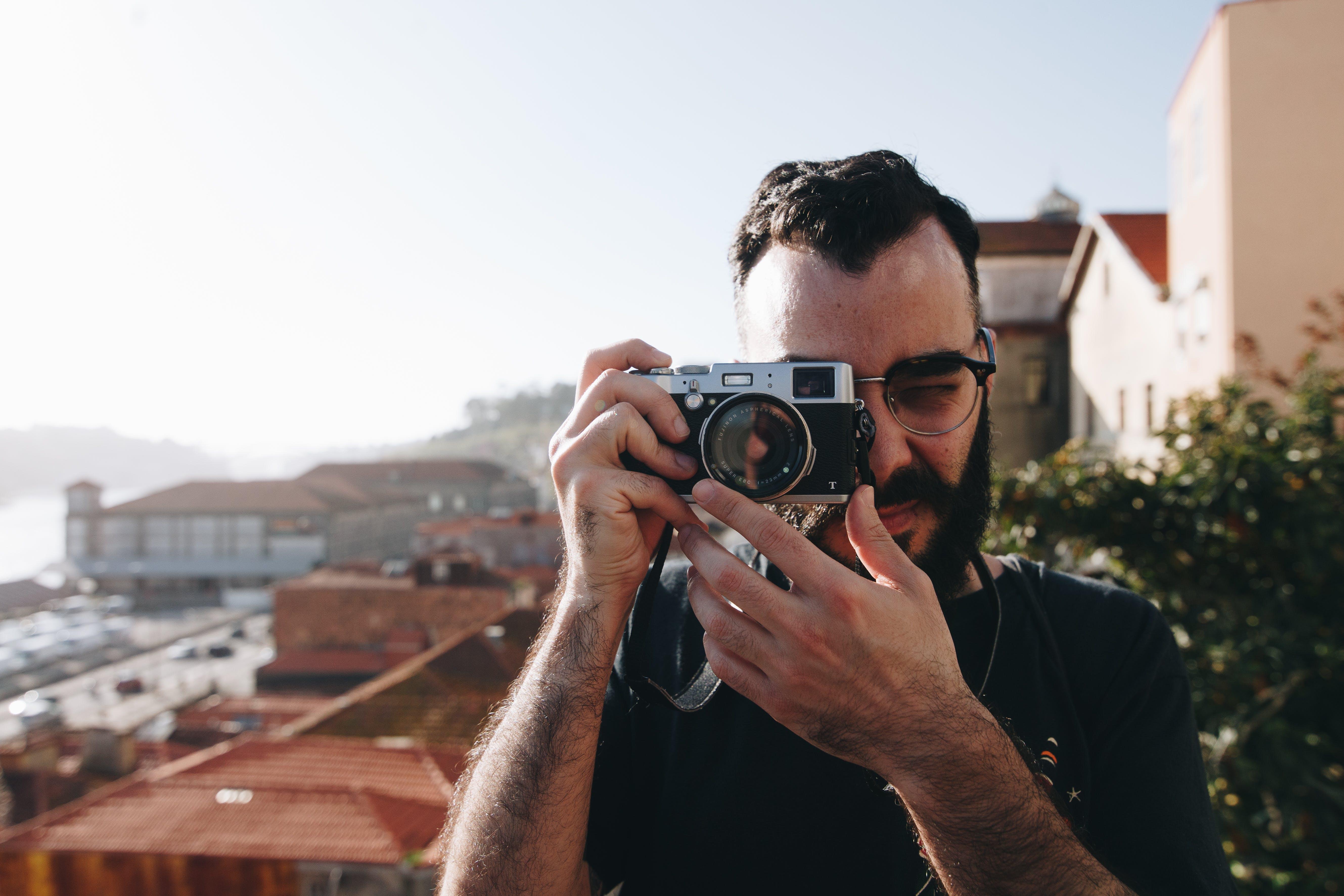 Man Holding Gray Point-and-shoot Camera