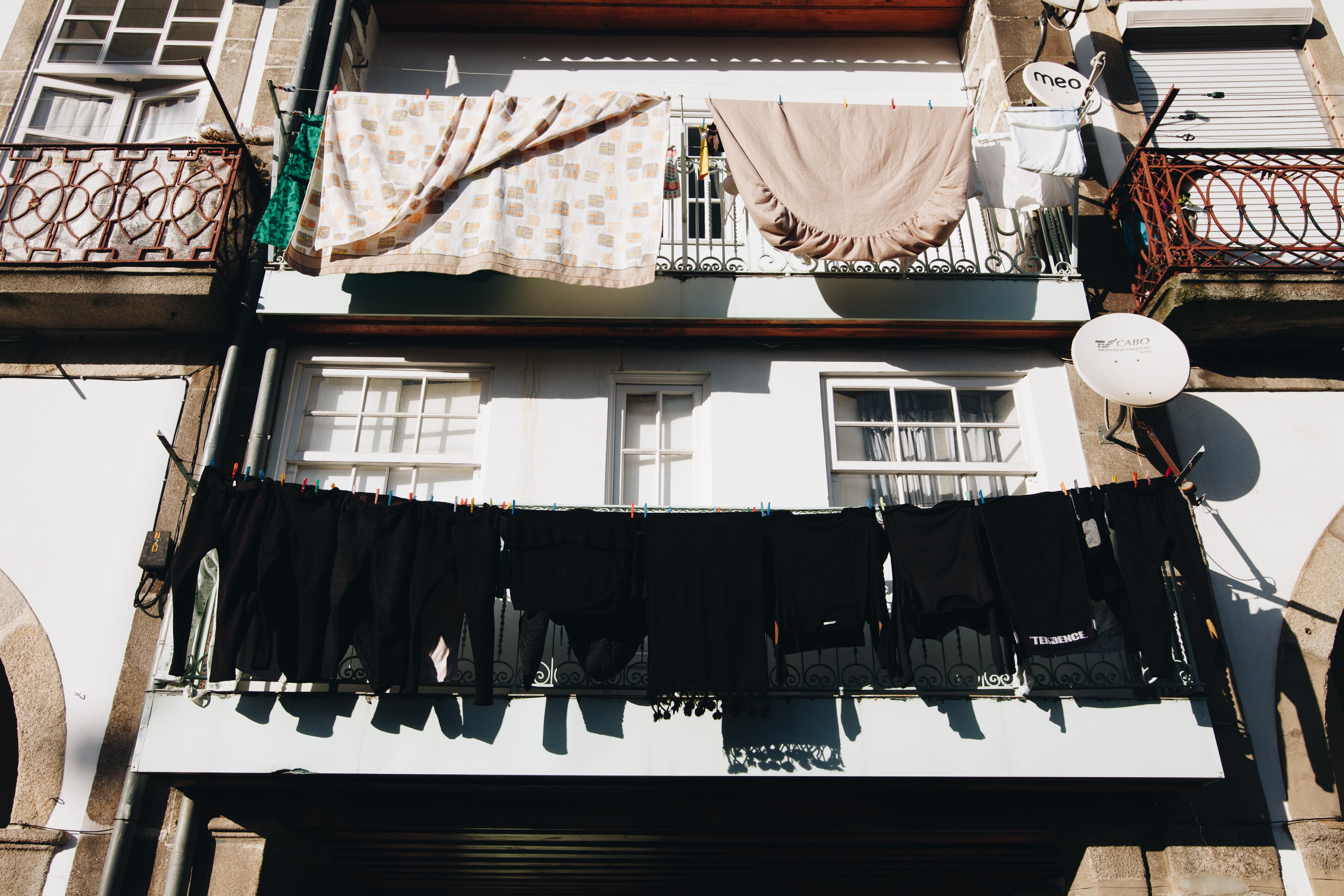 Close Up Photo of Black Clothes Hanged Outside Window