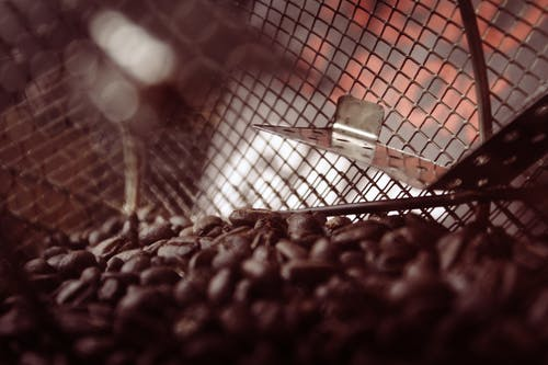 Shallow Focus Photography of Metal Frame and Coffee Beans