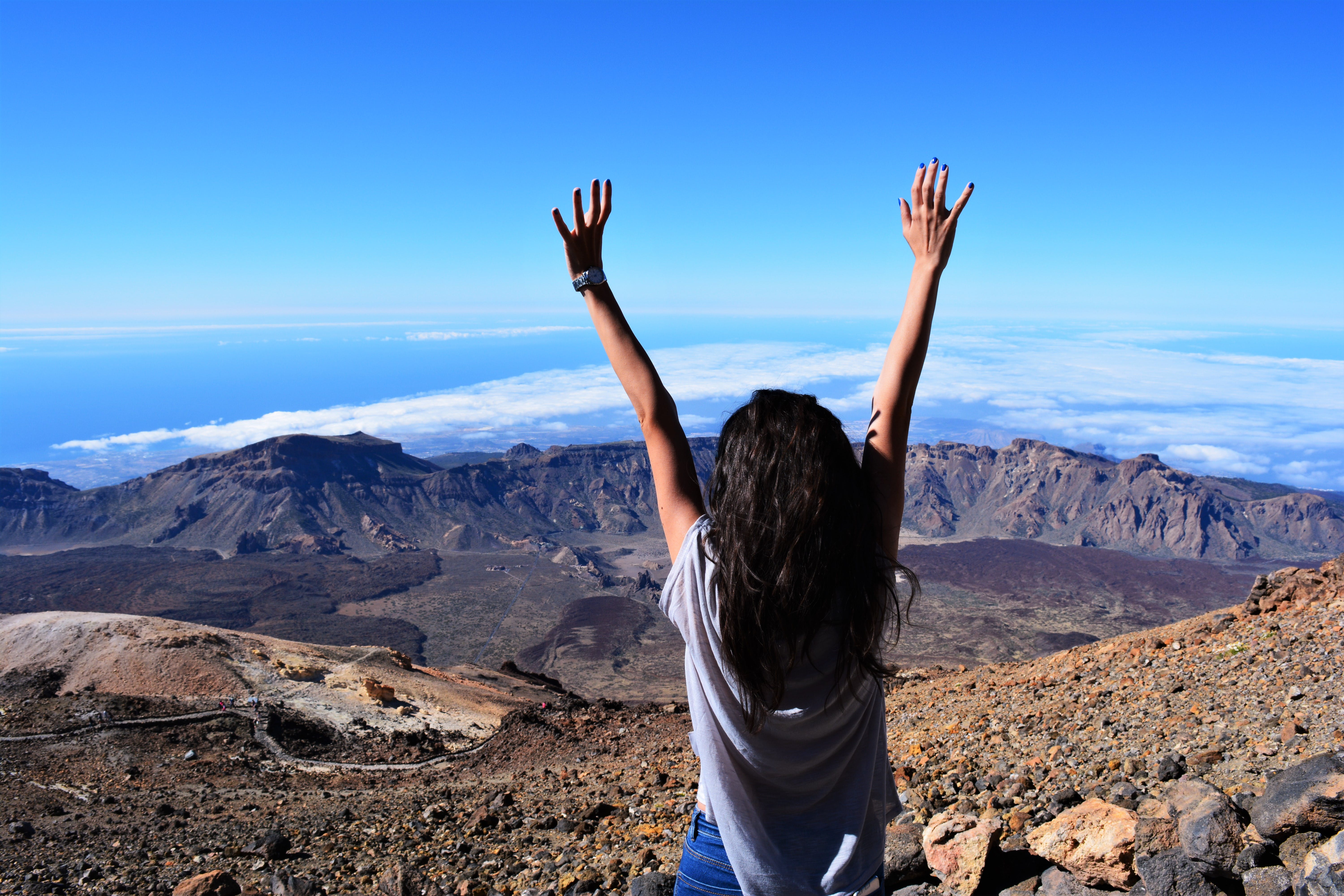 Woman Standing on Mountain While Raising Her Hands
