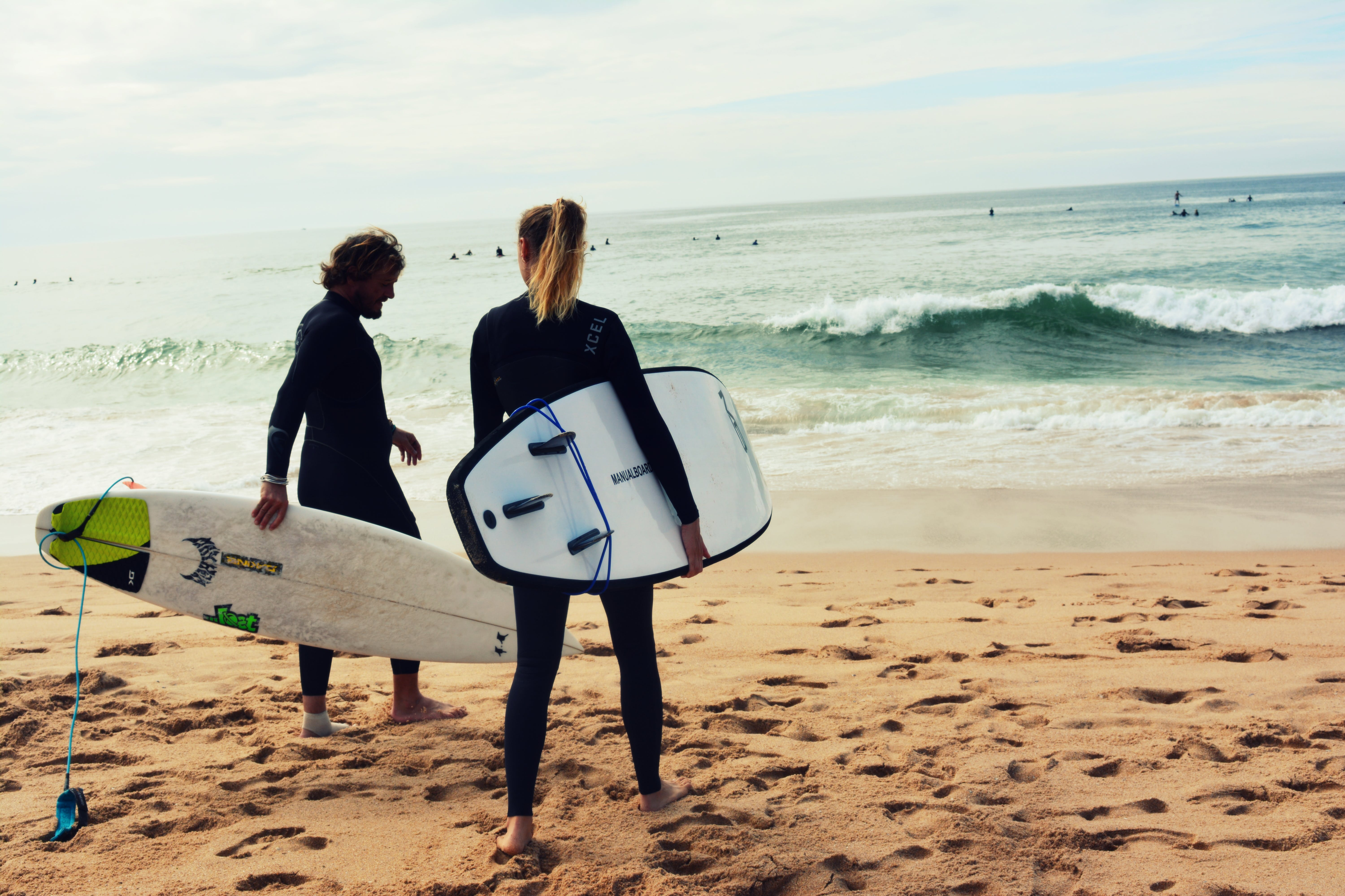 Man and Woman Holding Surfboards on Seashore