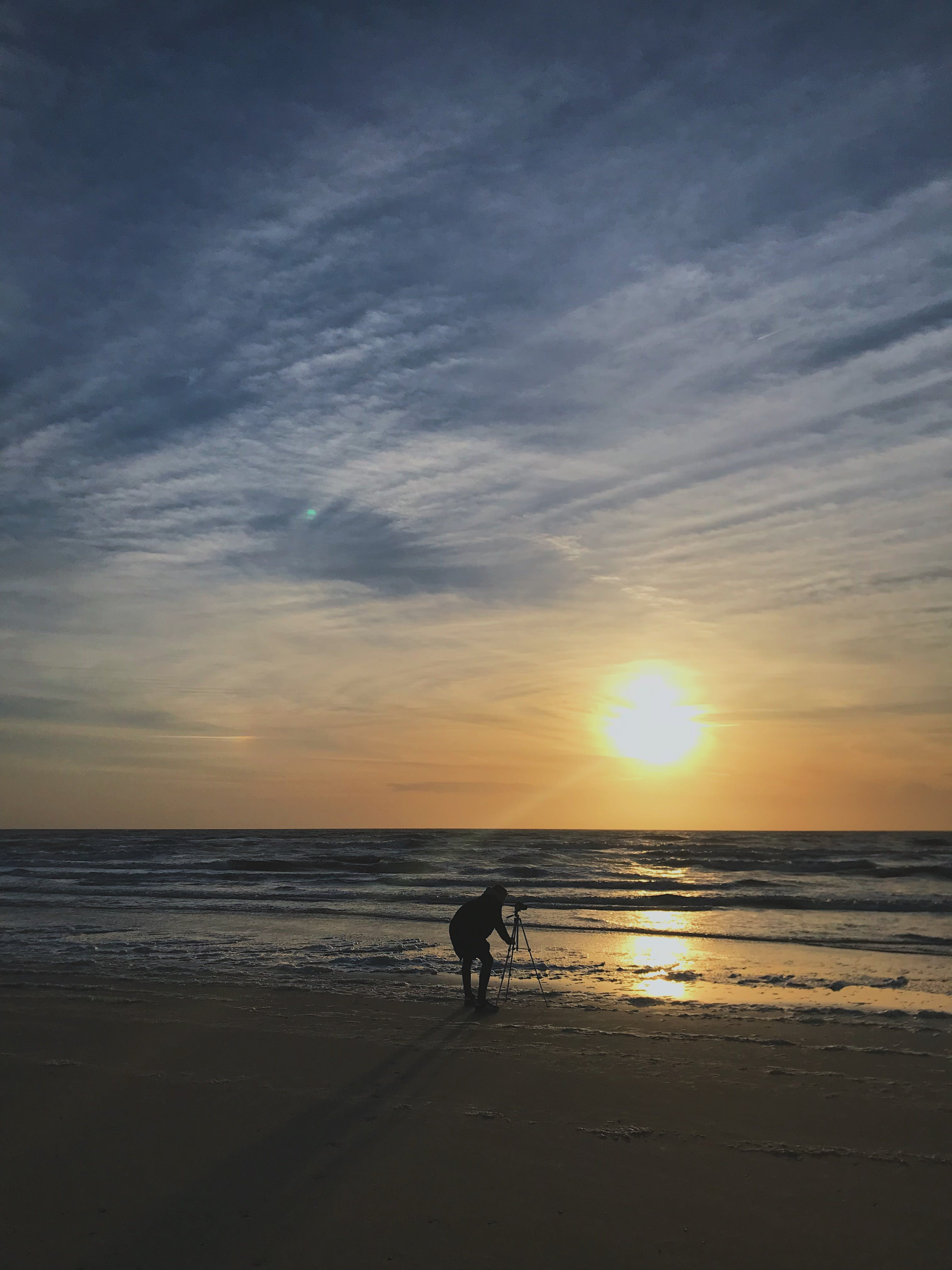 Silhouette Photo of Person Placing Tripod Stand on Seashore