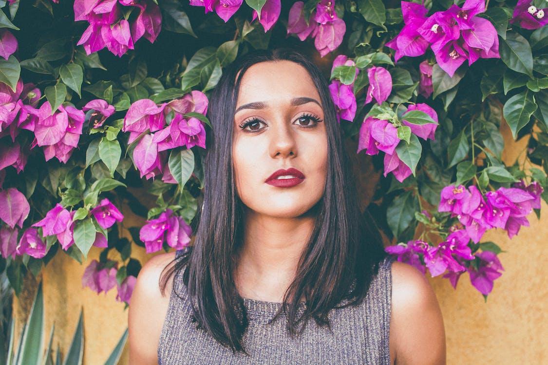 Woman in Gray Scoop-neck Sleeveless Top Standing in Front of Purple Flowers