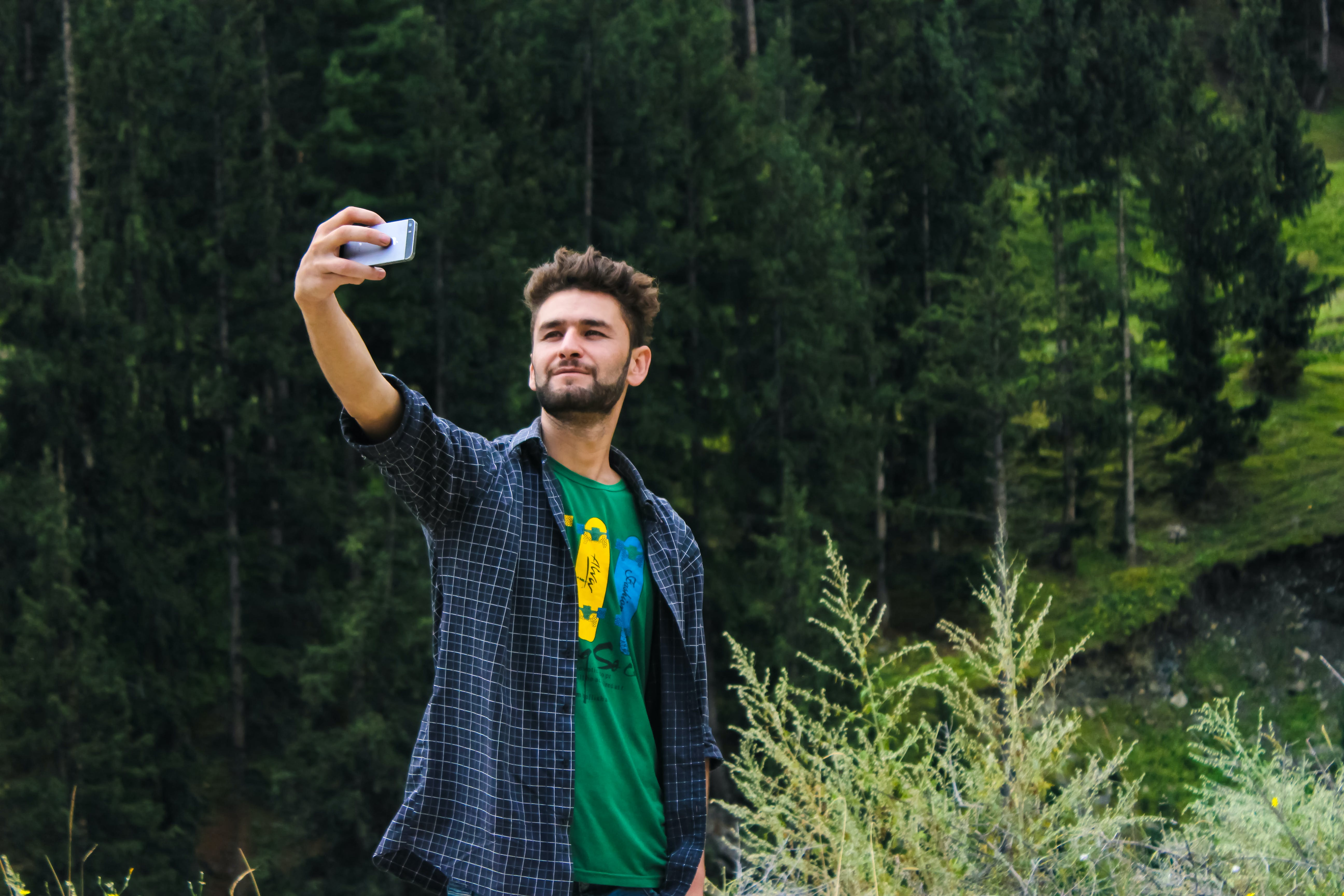 Man in Blue Sports Shirt and Green Top Taking a Selfie Near Green Trees