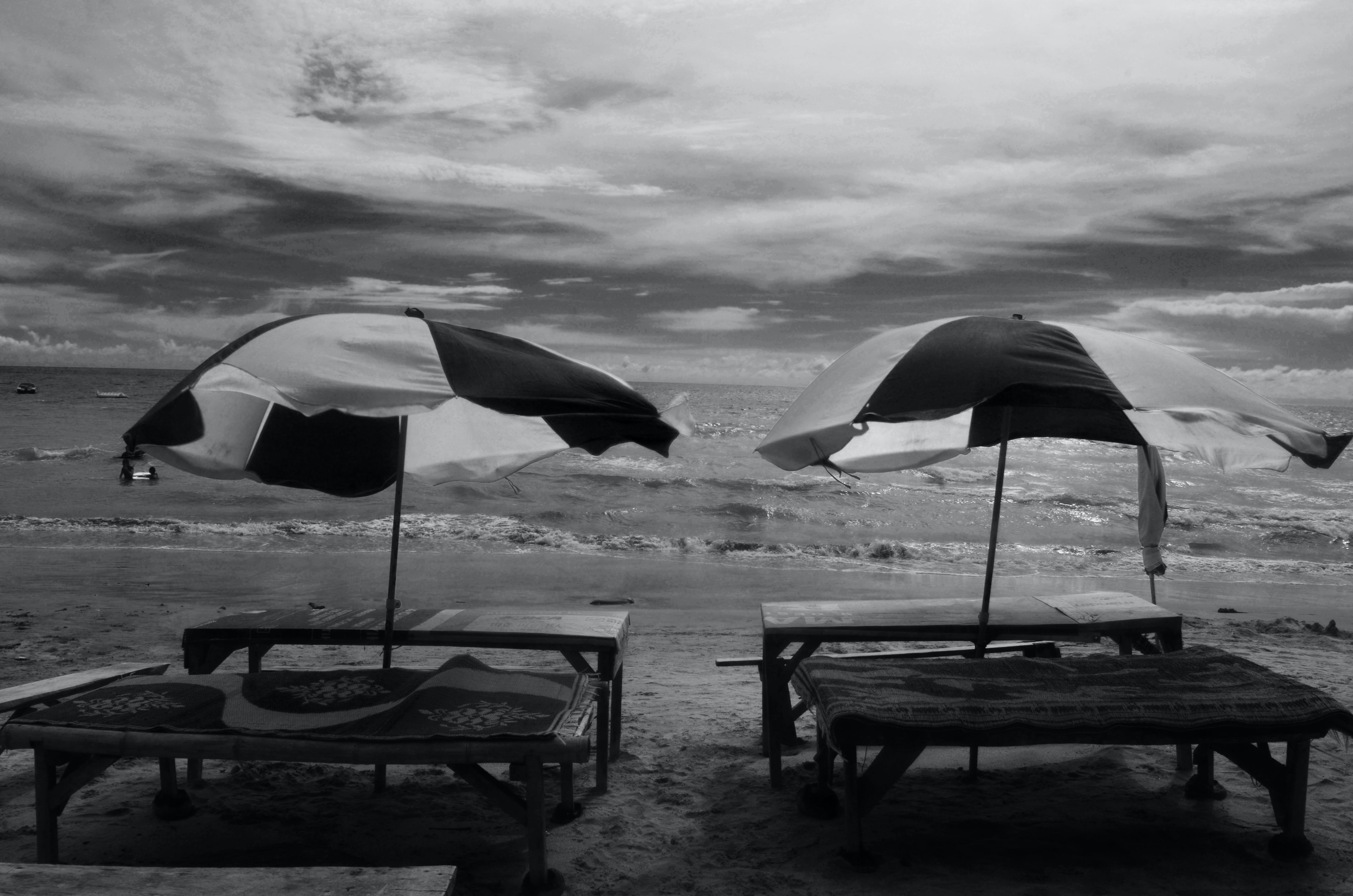 Grayscale Photography of Two Picnic Tables on Seashore