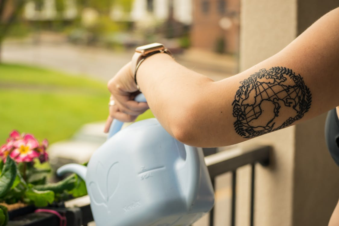 Person Holding Gray Plastic Watering Can