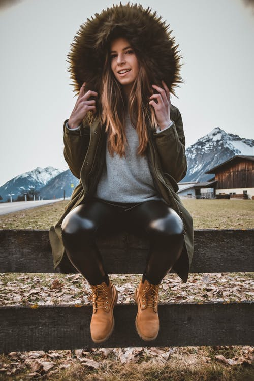 Woman Wearing Brown and Green Parka Sitting on Gray Wooden Fence at Daytime