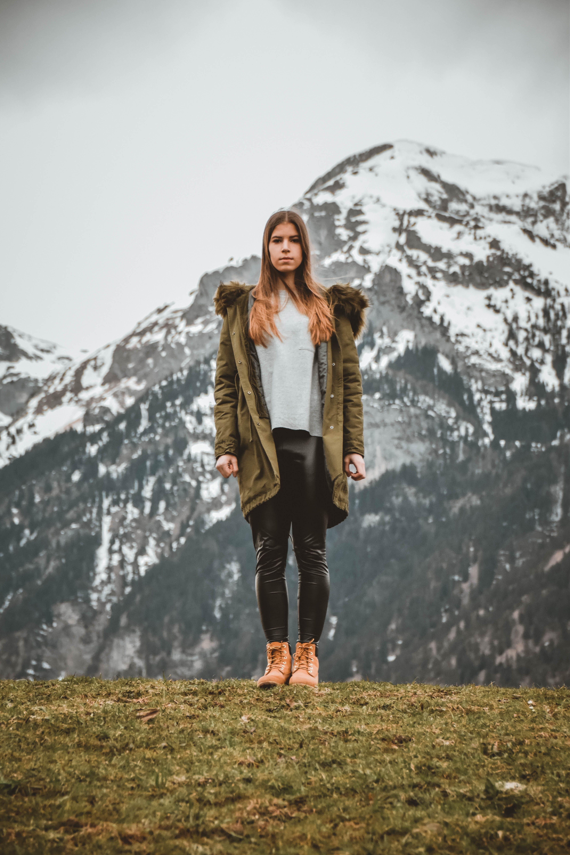Woman Wearing Green Jacket in Front of Snowy Mountain