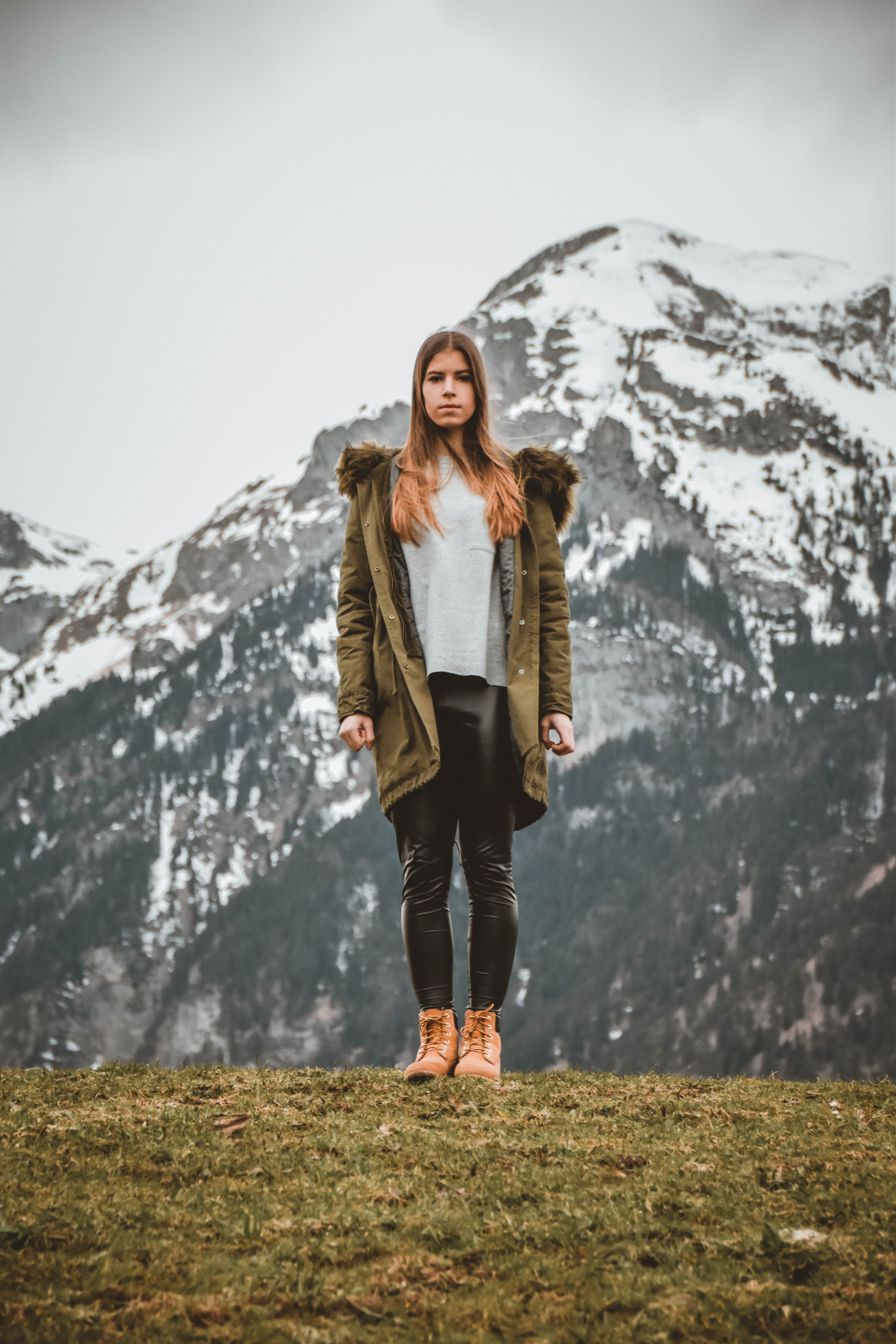 Woman Wearing Green Jacket in Front of Snowy Mountain