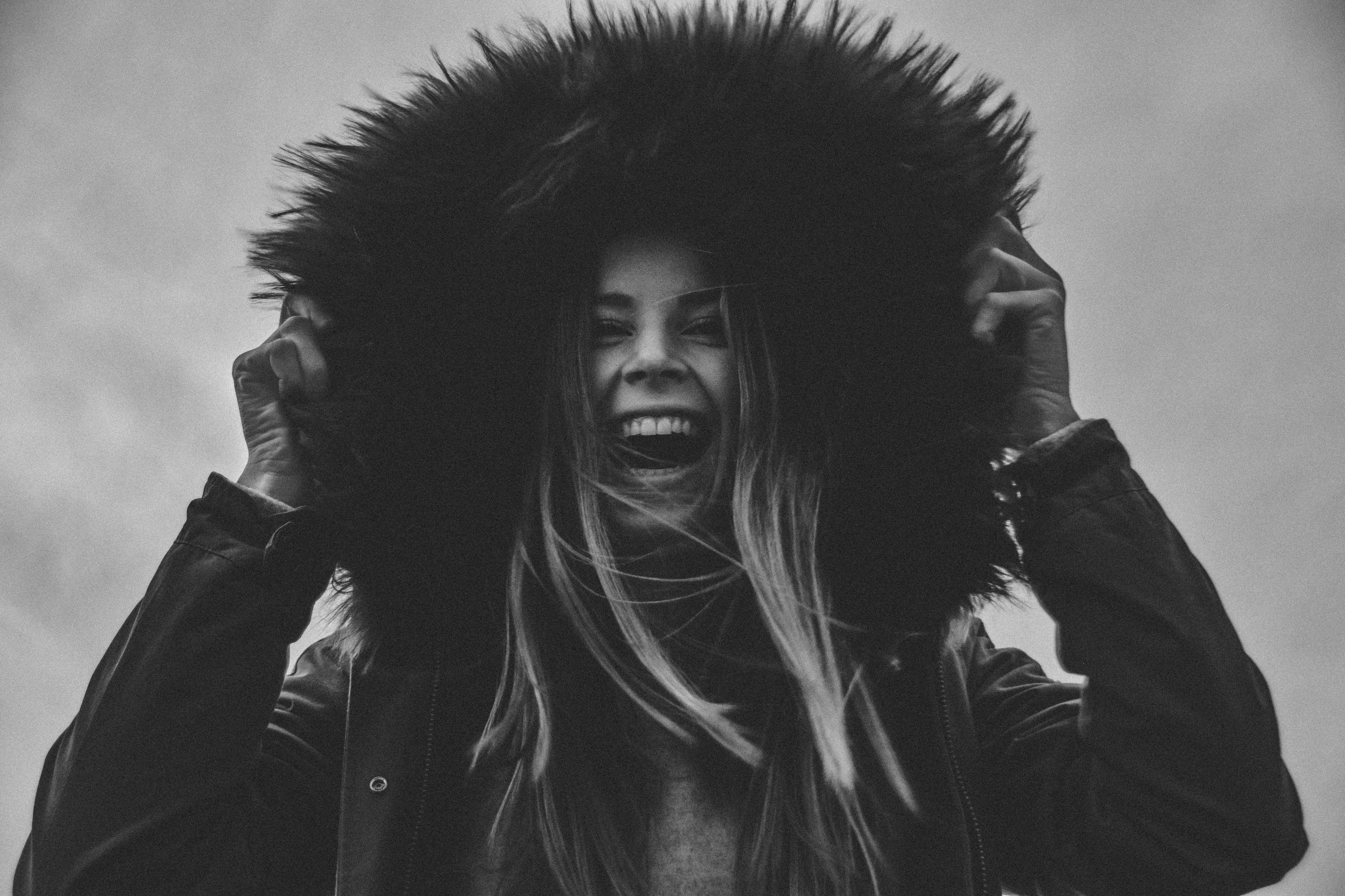 Grayscale Photo of Laughing Woman Holding Her Hat