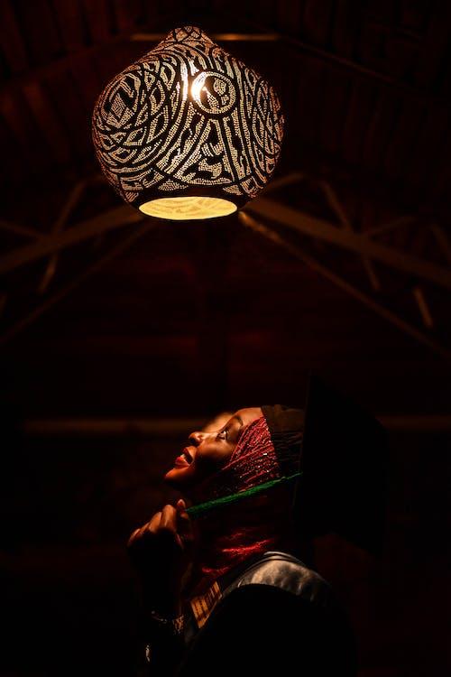 Woman Looking Upwards Toward Pendant Lamp
