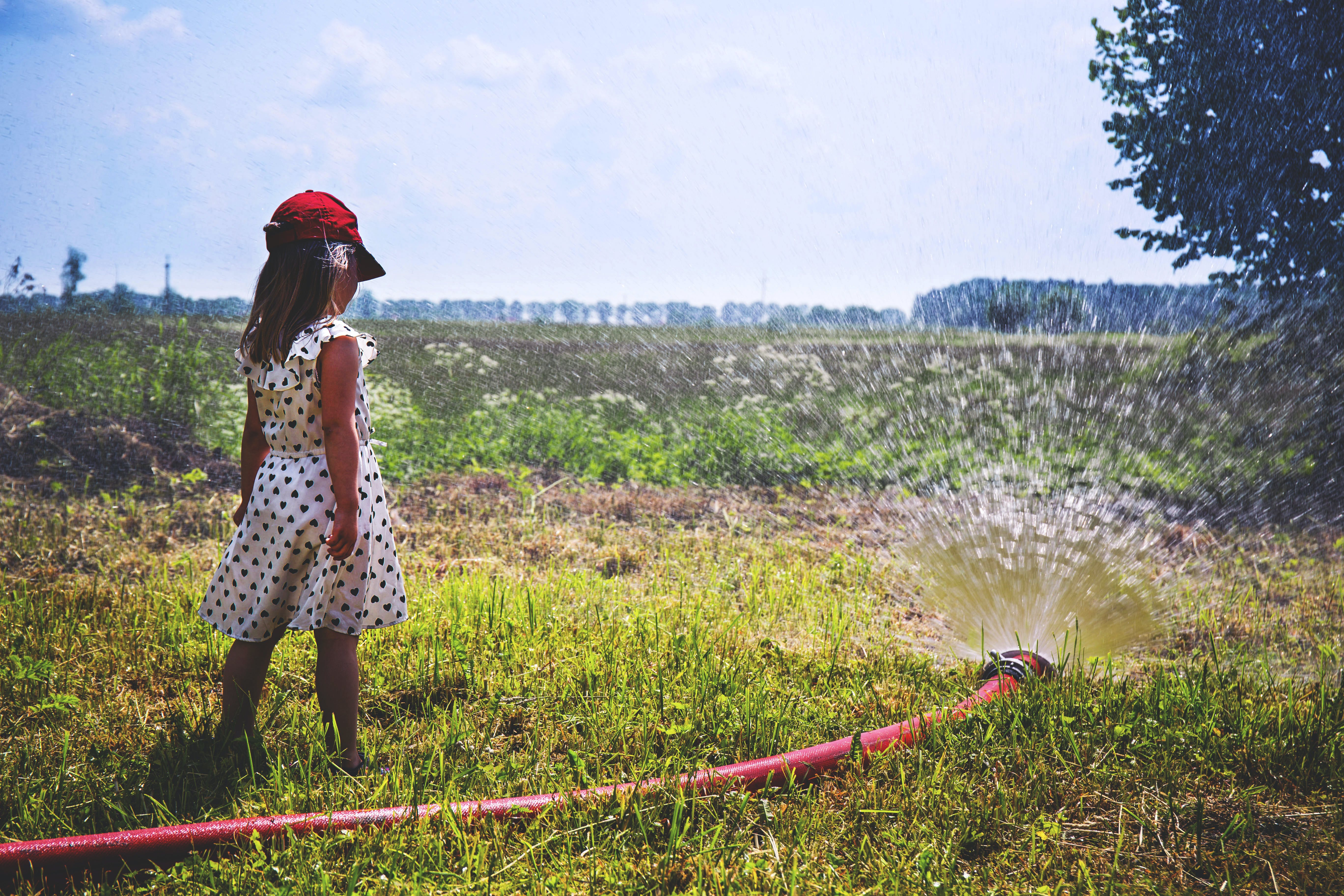 Girl on Green Grass Near Red Hose While Pumping Water during Daytime