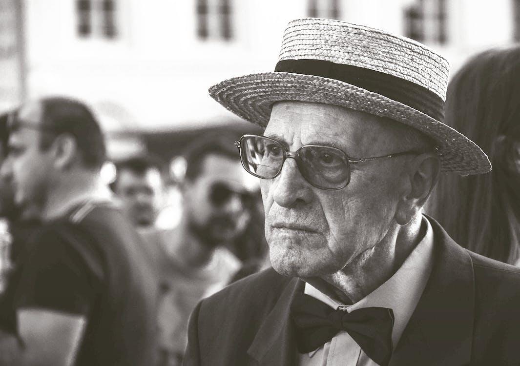 Homem Com Chapéu De Palha E Gravata Borboleta Com Pessoas