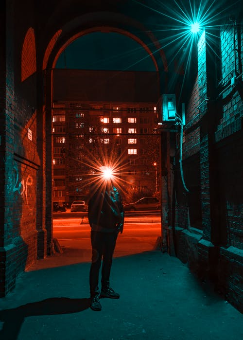 Photo of Man in Jacket Standing in Alley