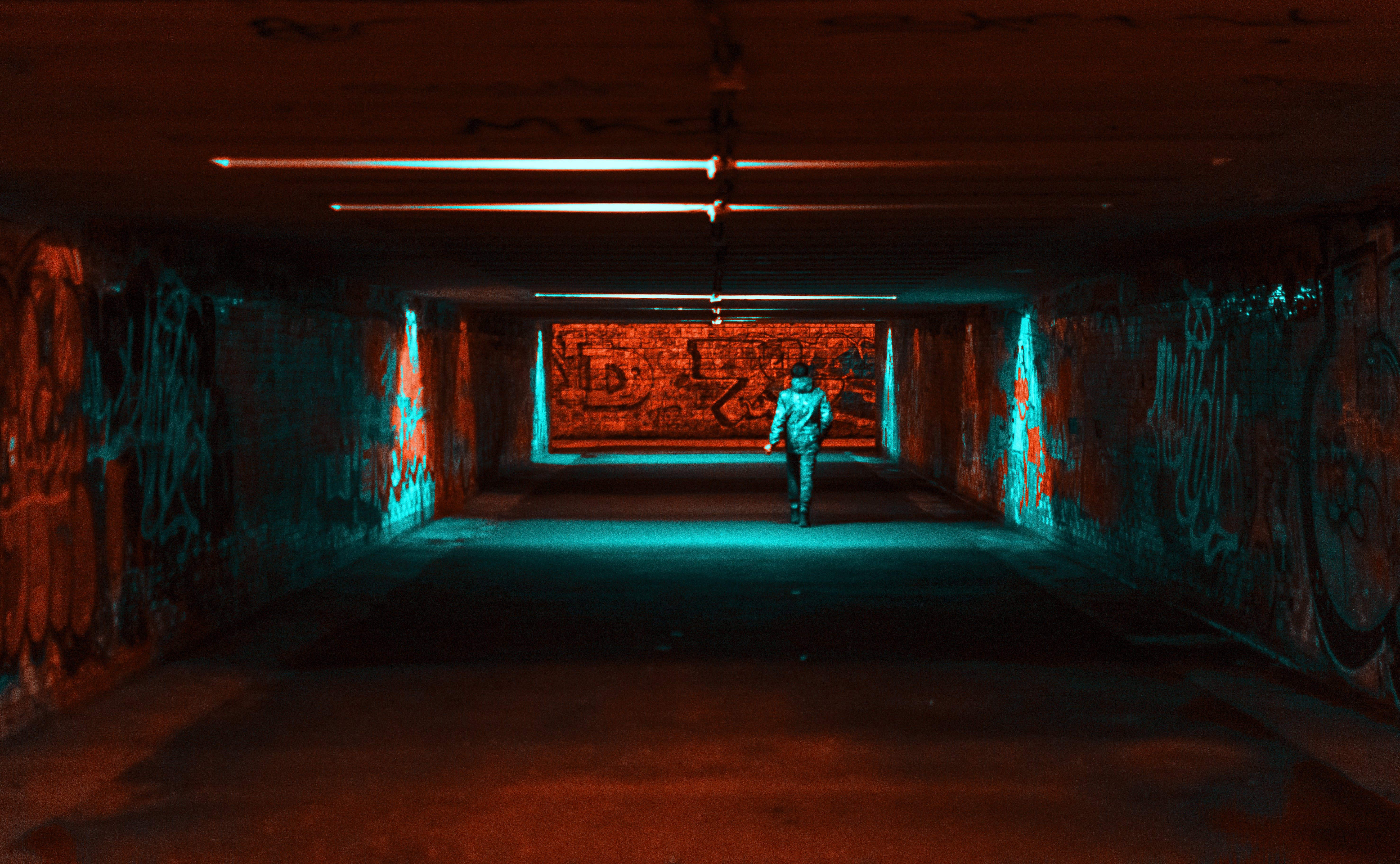 Person Wearing Jacket Walking on Tunnel With Red and Green Lights
