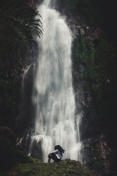 Photo of Man Sitting Near Waterfalls
