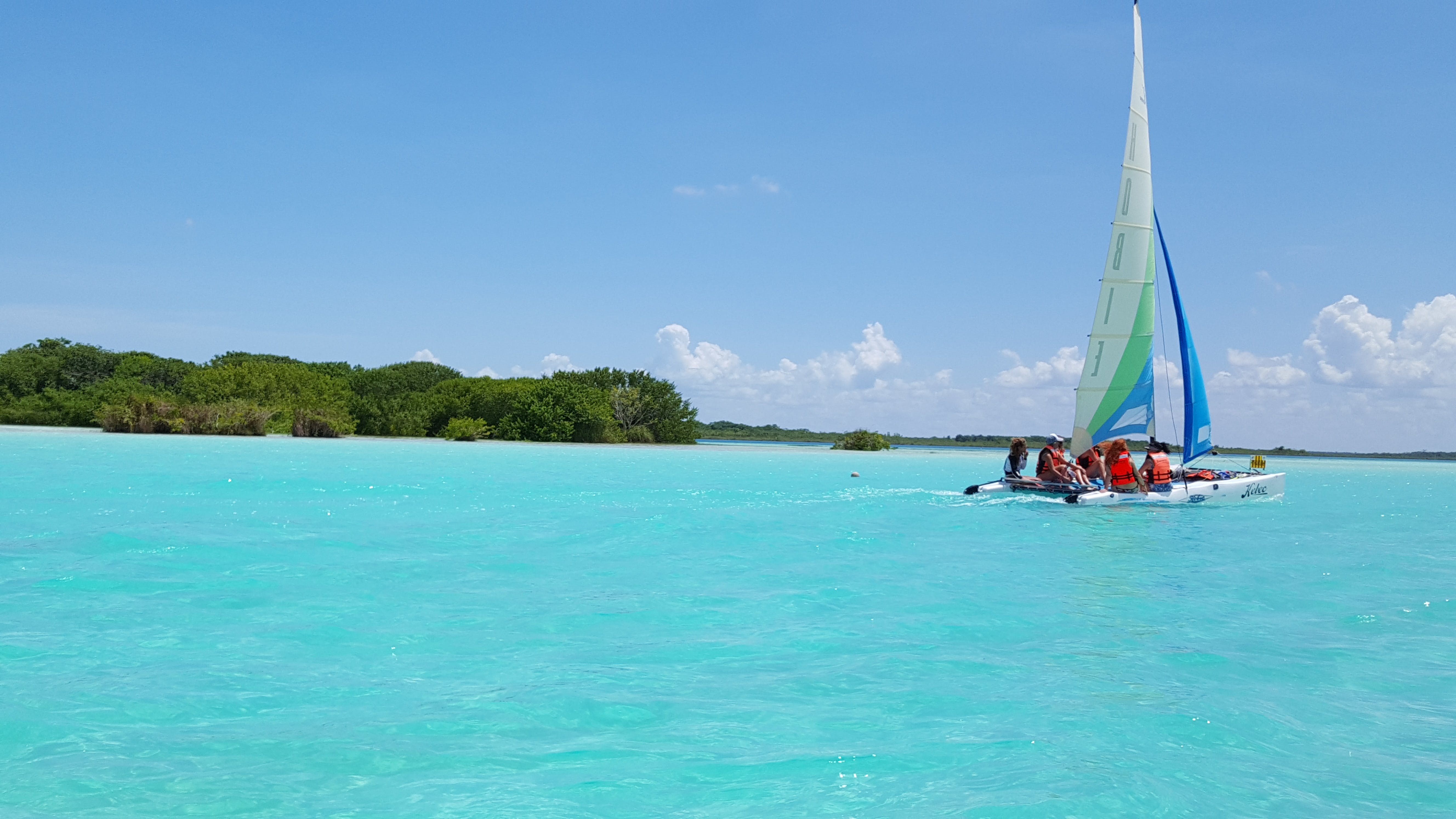 Group of People Riding Sailboat on Body of Water