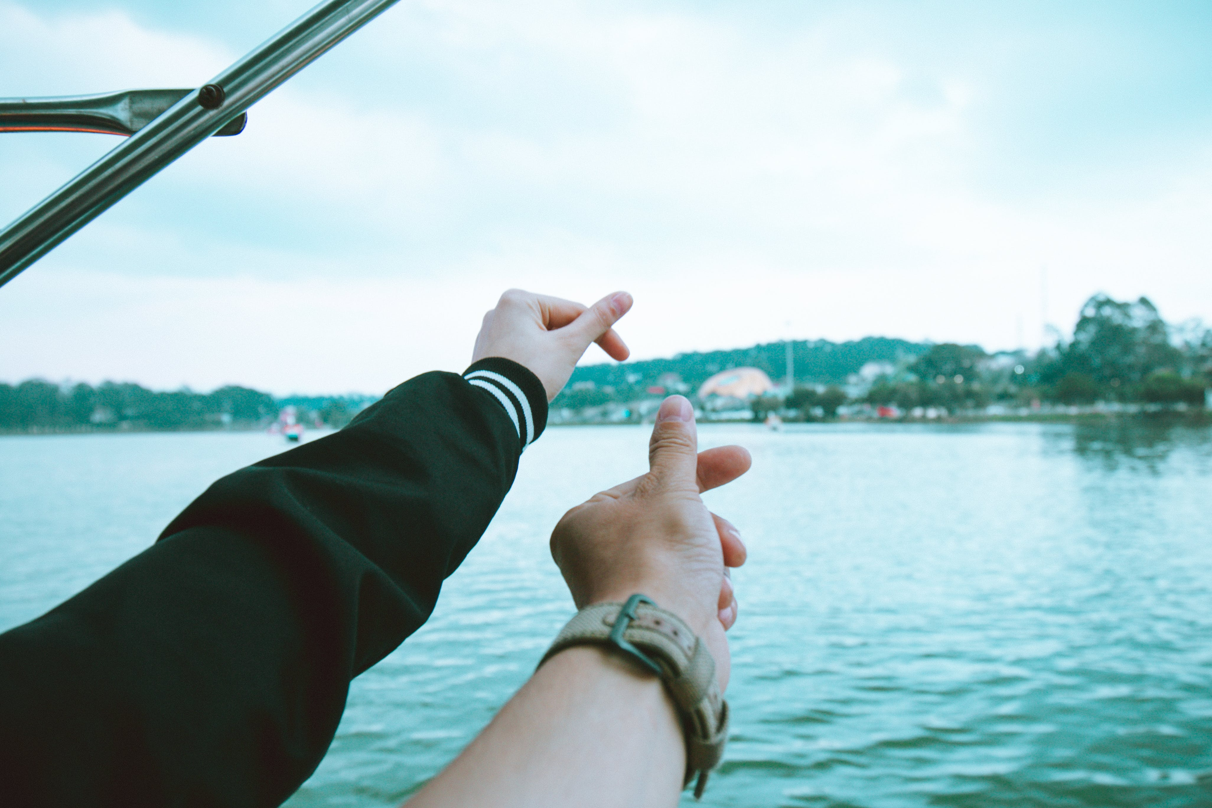 Two Person's Left Hand Making Finger Heart Sign Near Body of Water