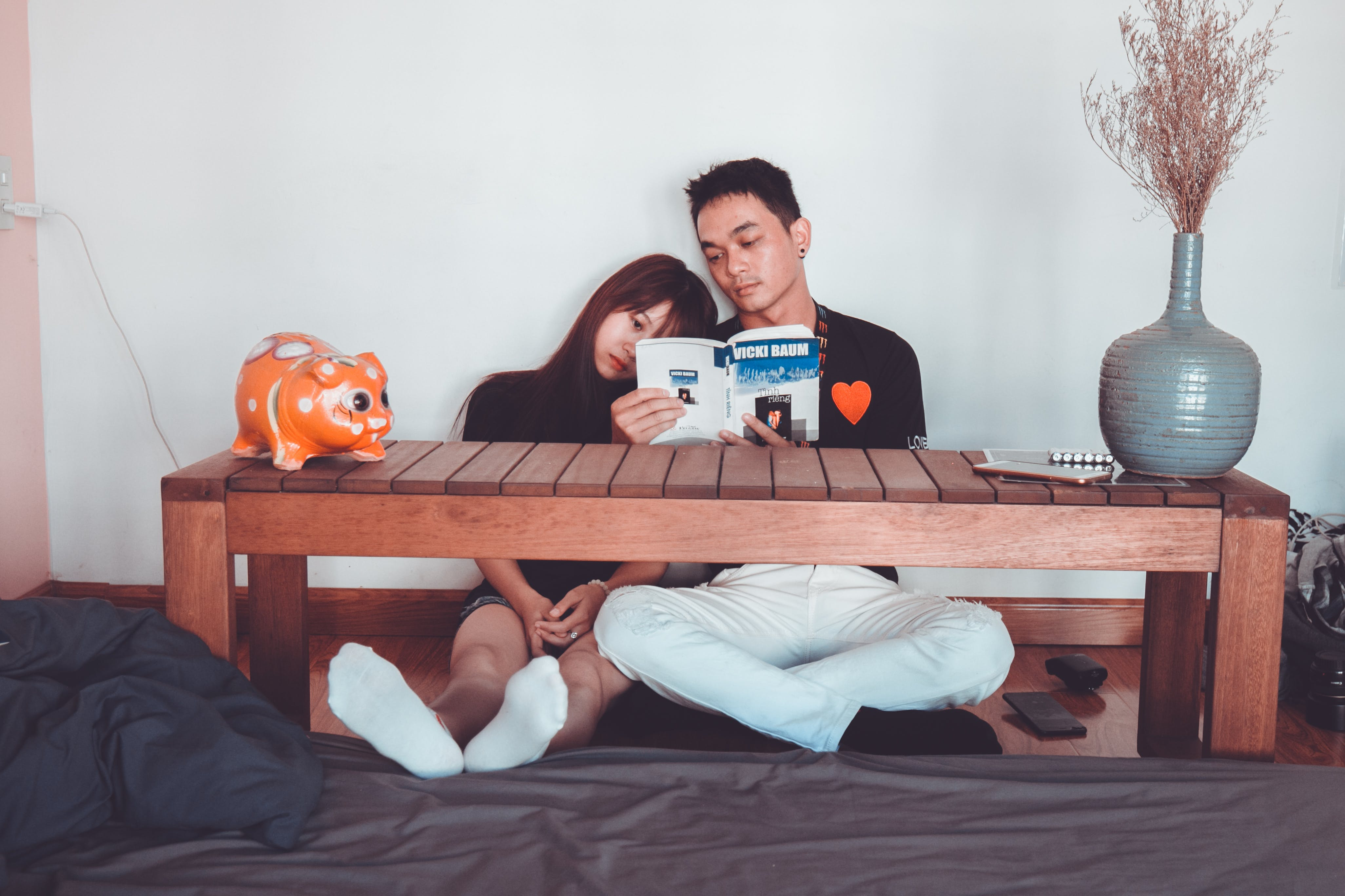 Couple Reading Book Sitting on Front of Rectangular Brown Wooden Coffee Table