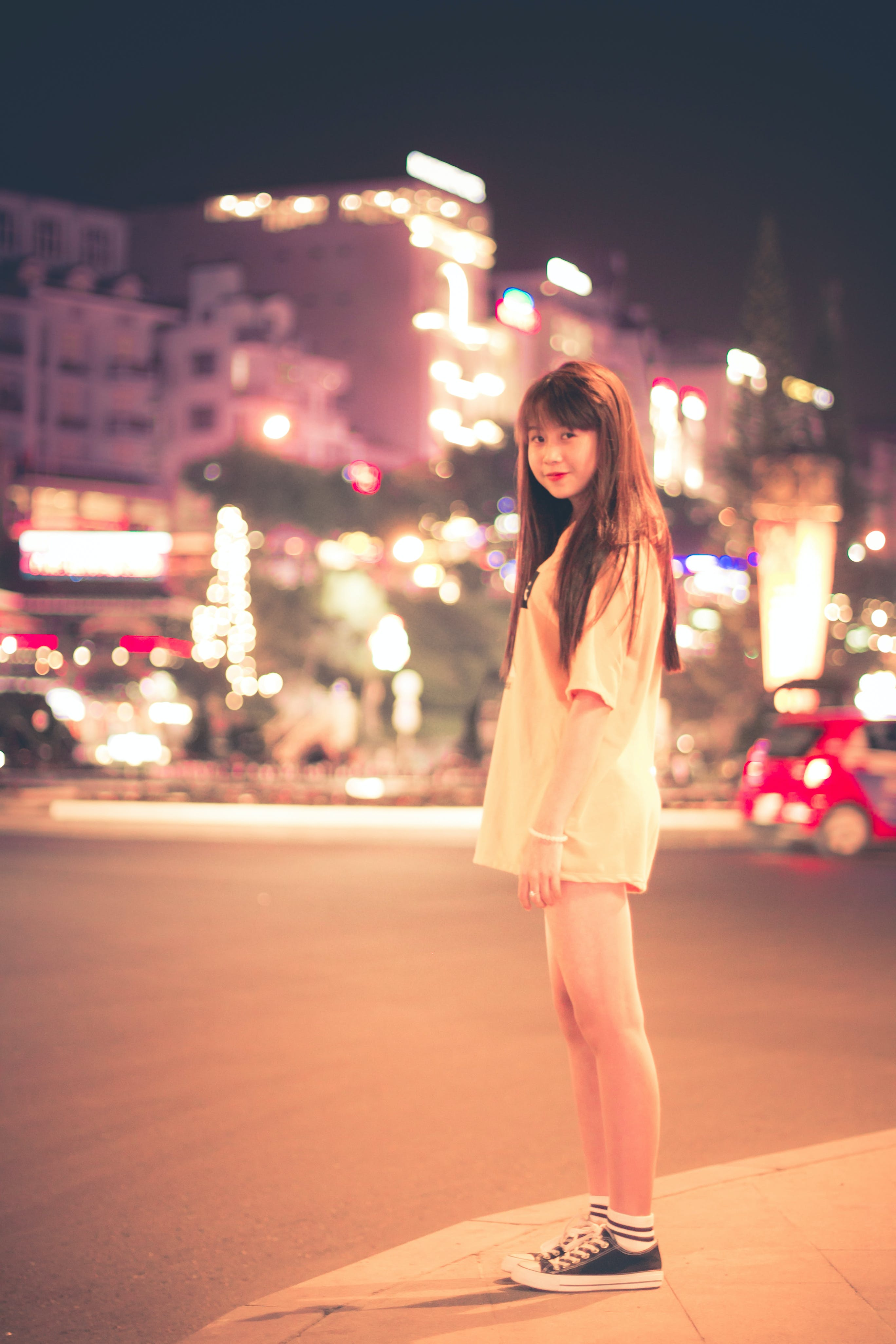 Woman in White Shirt Standing on Roadside during Night Time