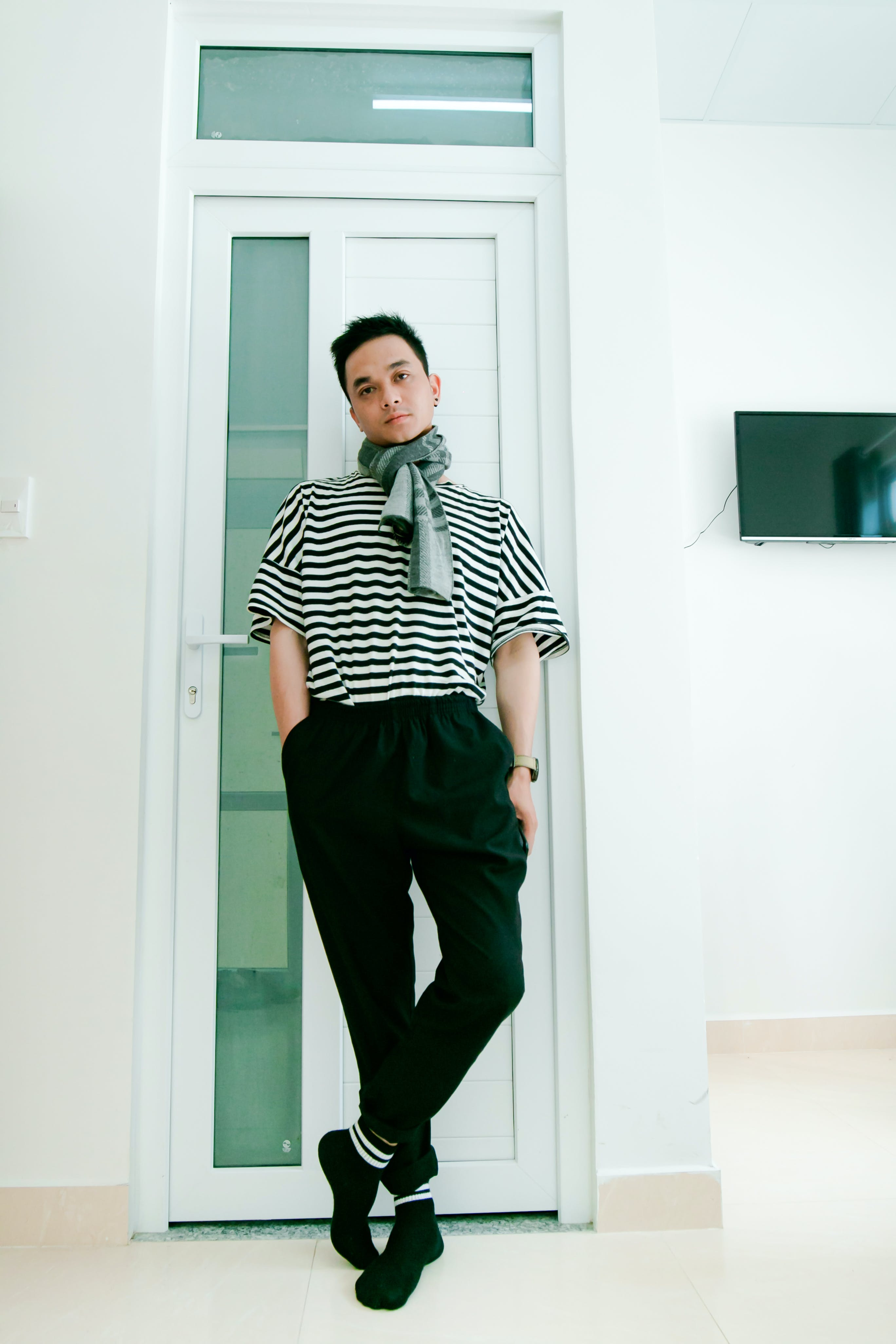 Man in Black and White Striped Shirt Leaning on Door