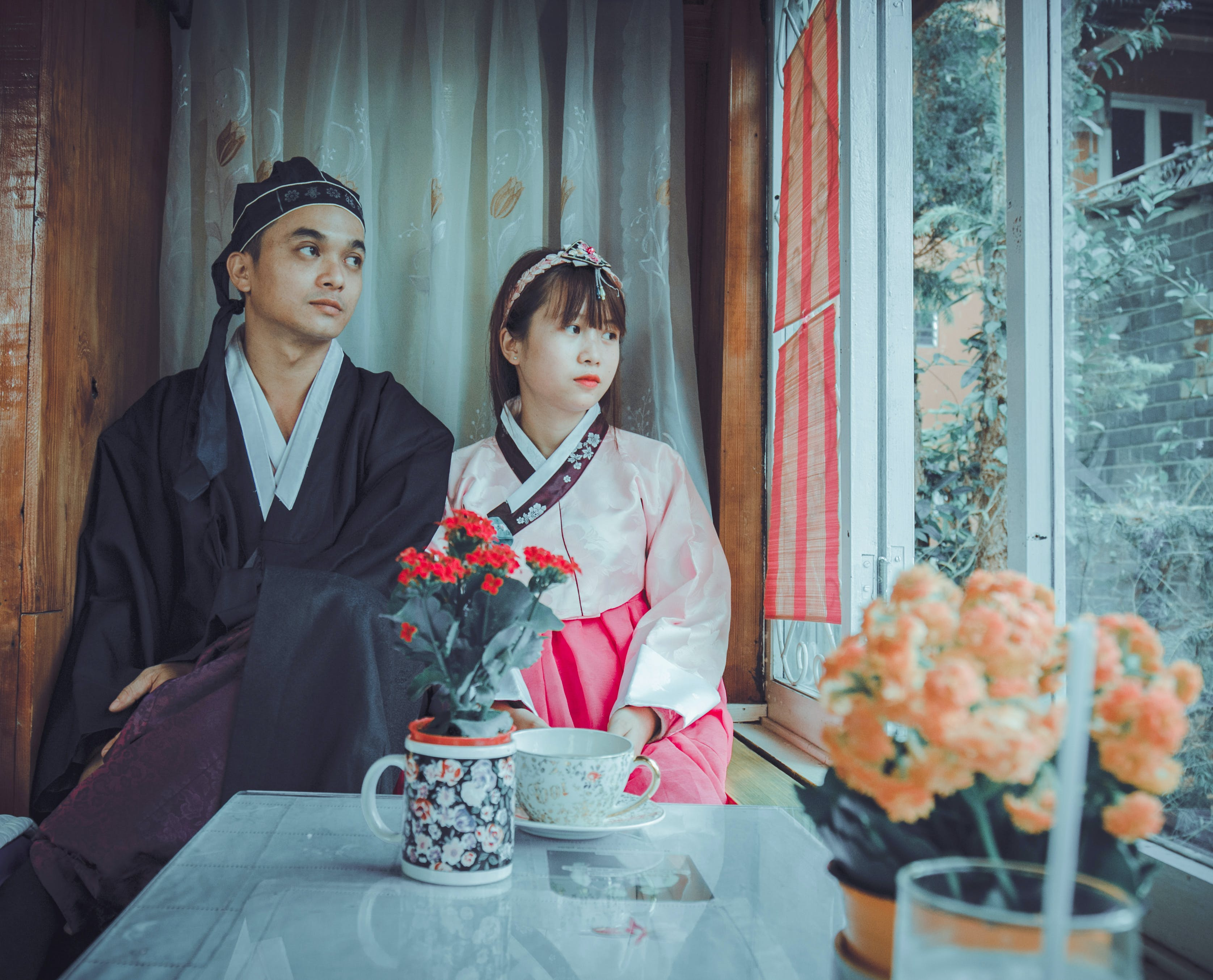 Couple Wearing Korean Traditional Dress Near Windowpane Staring at the Window