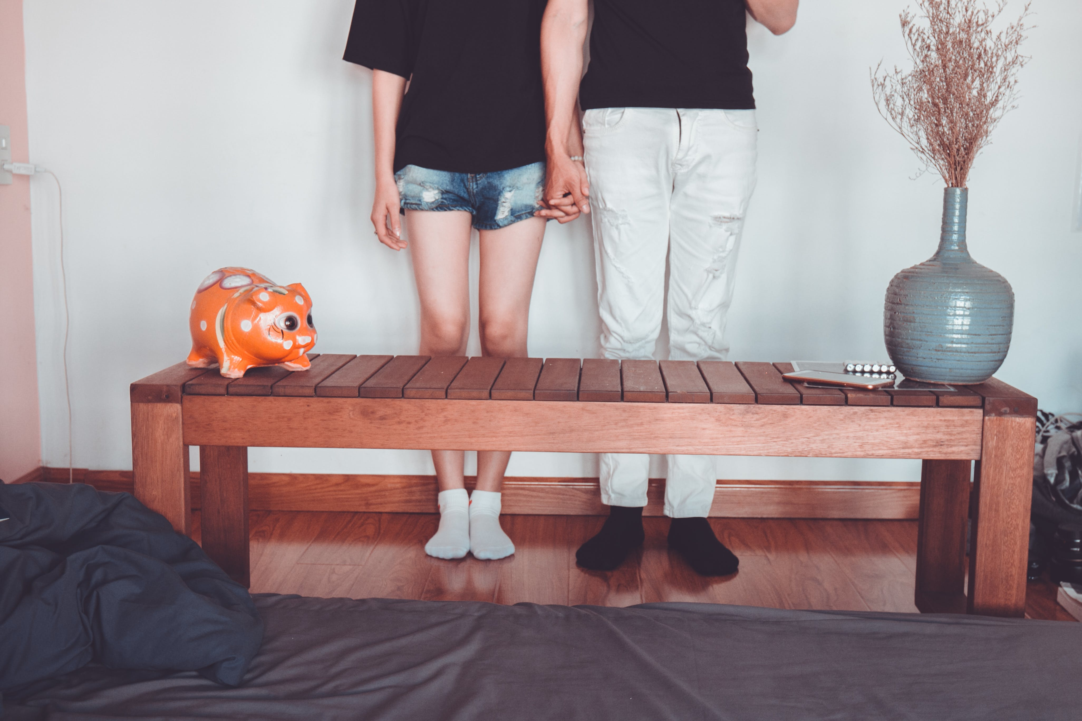 Woman and Man Holding Hand Standing Near Brown Coffee Table Inside Room