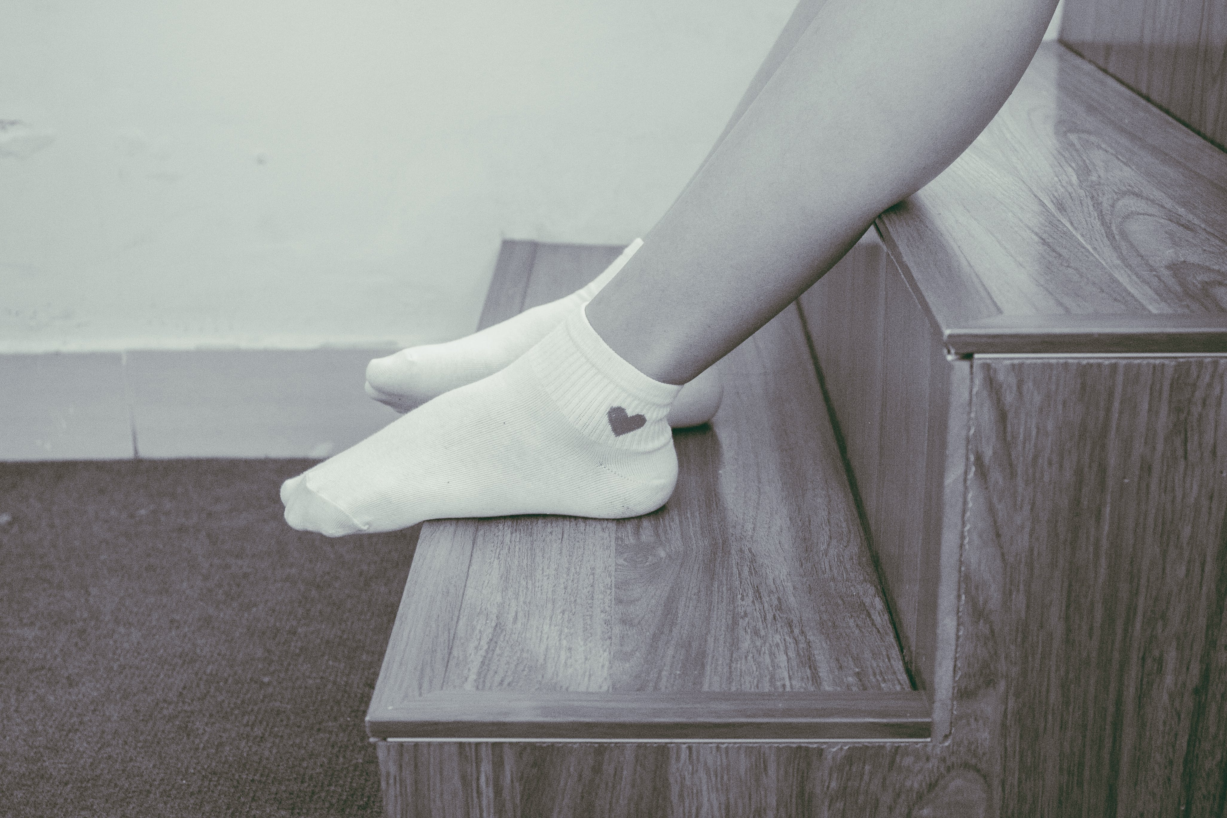Person Wearing Pair of Foot Socks Sitting on Staircase