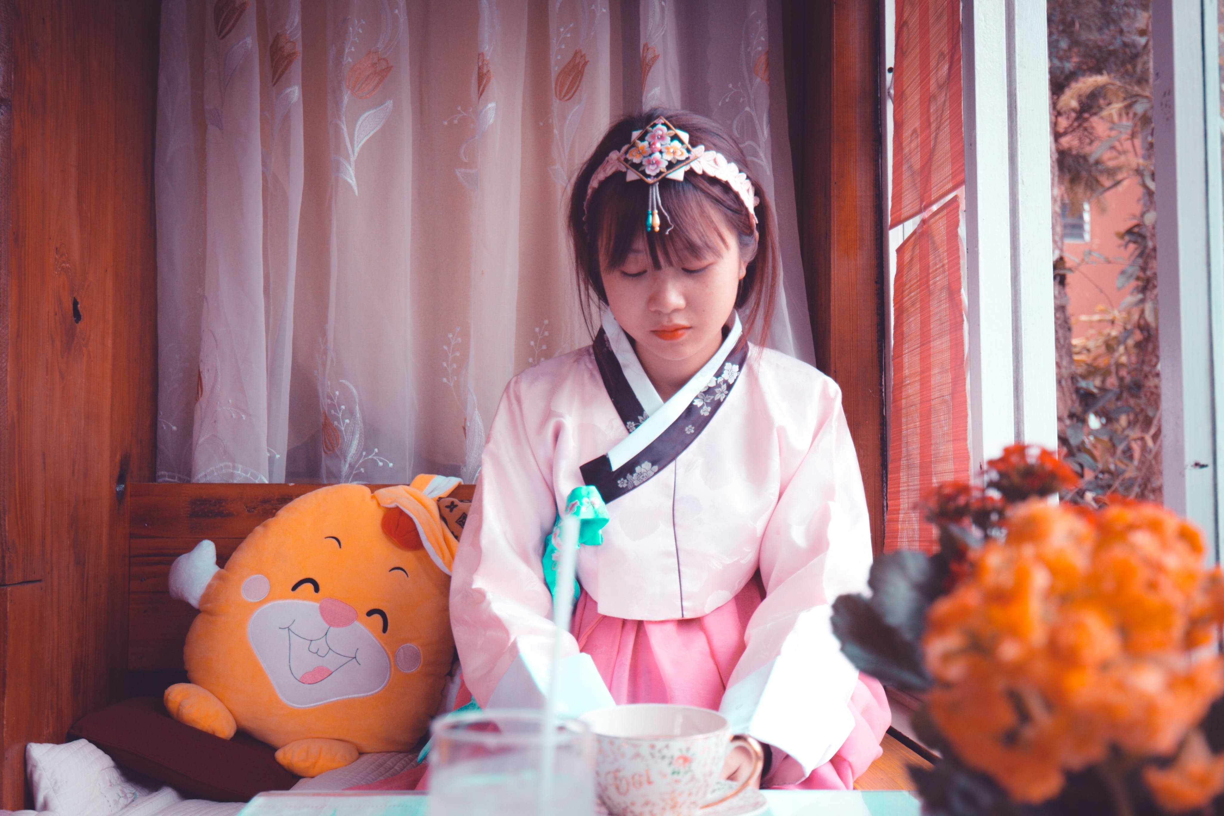 Woman Wearing White and Pink Traditional Korean Dress Sitting Near Yellow Plush Toy