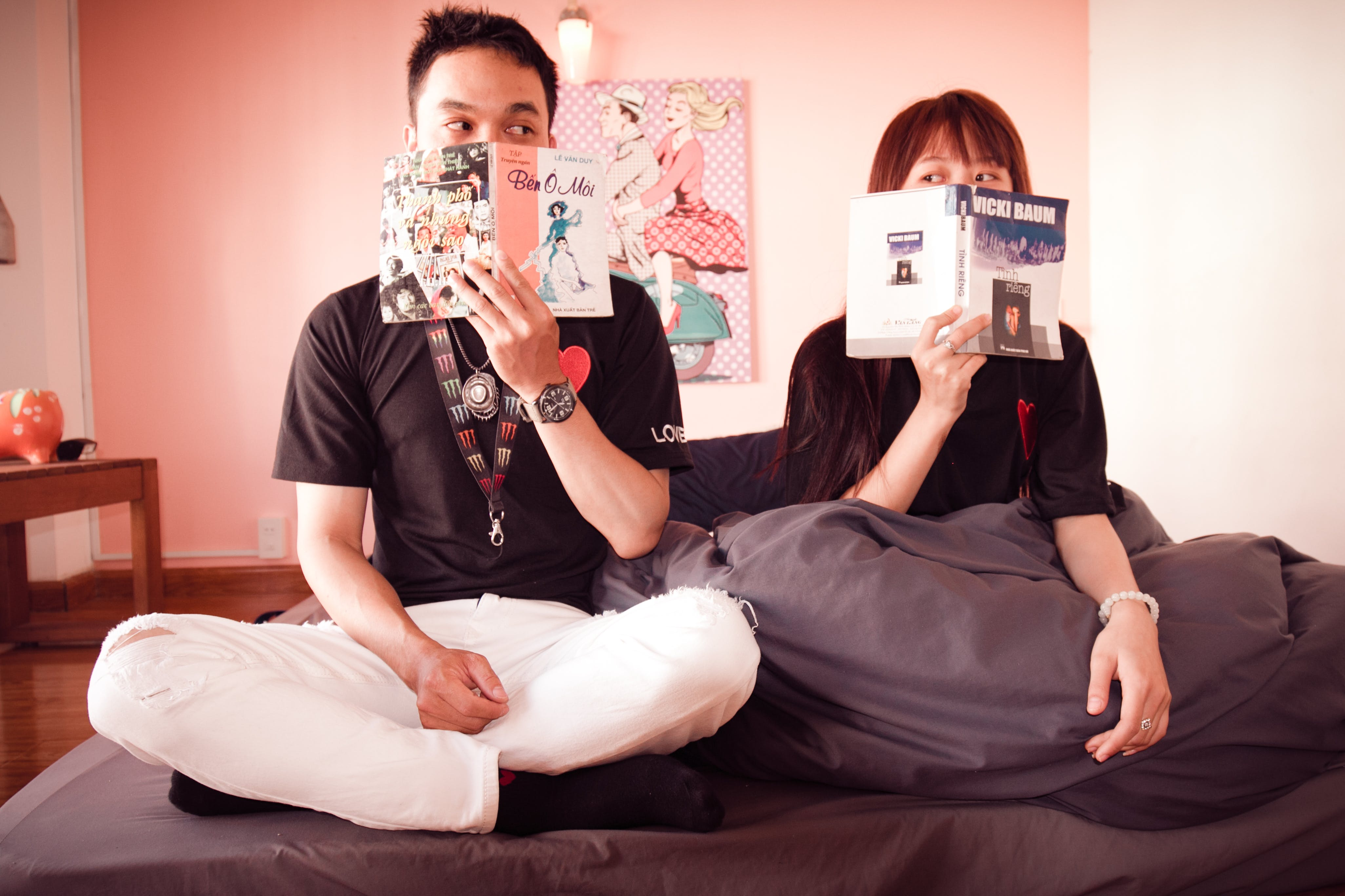 Couple Holding Books Sitting on Bed