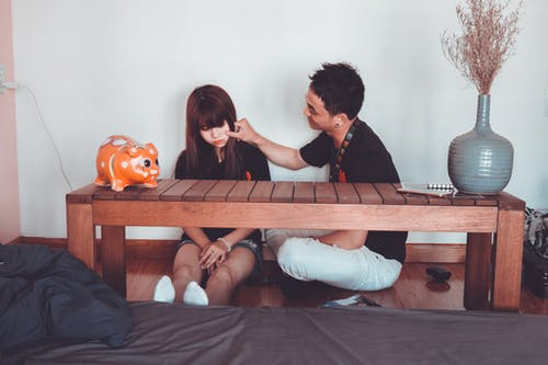 Man Pinching the Cheek of Woman Sitting Near Rectangular Brown Wooden Coffee Table