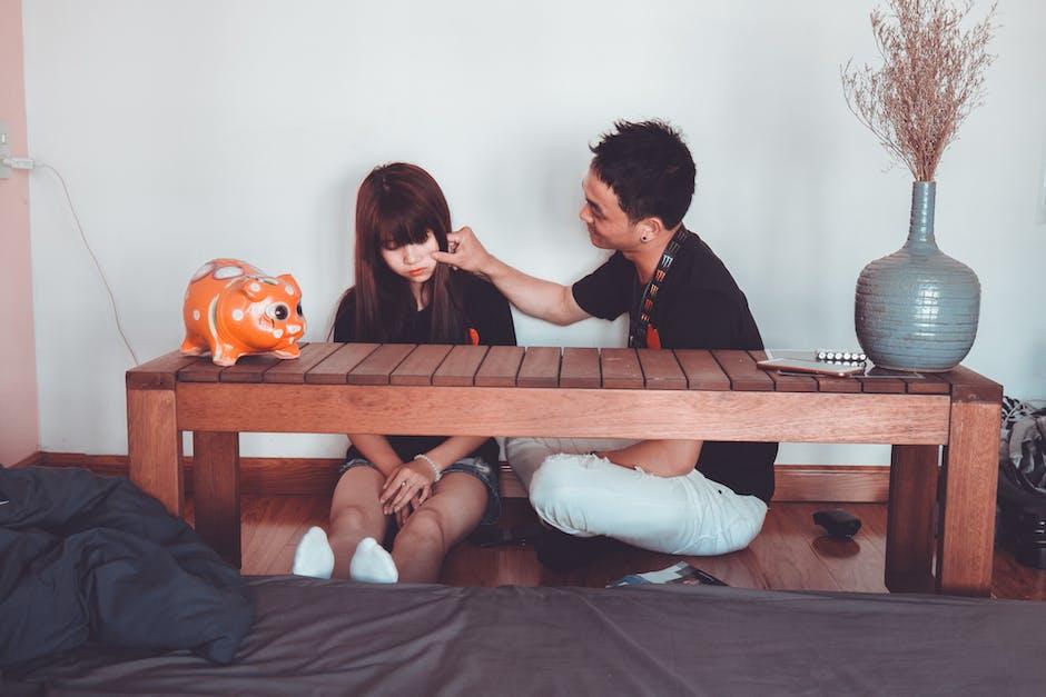Man Pinching the Cheek of Woman Sitting Near Rectangular Brown Wooden Coffee Table