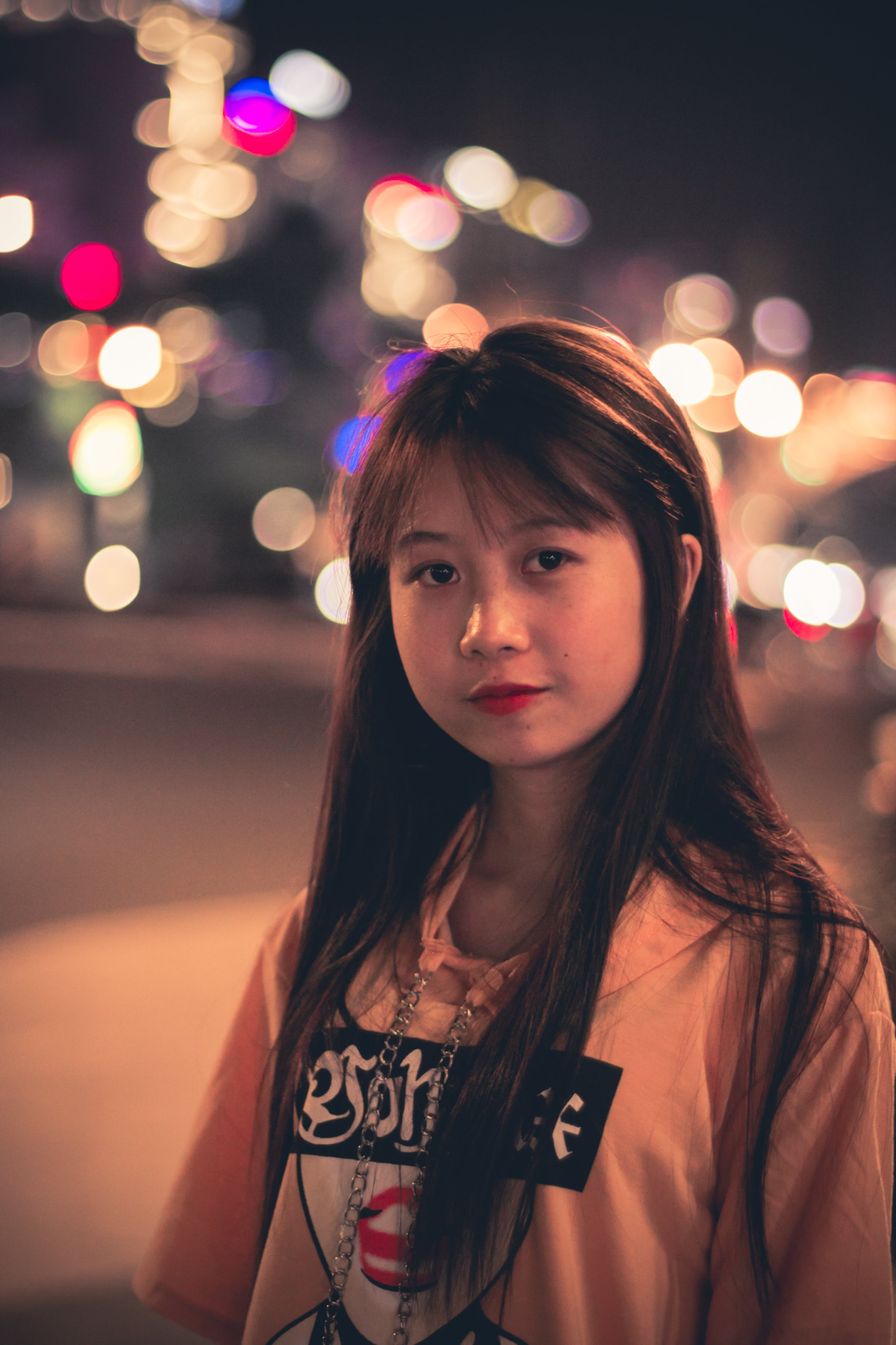 Woman Wearing Pink, Black, and Red Printed Pullover Hoodie Standing Beside Road Bokeh Photography at Night Time