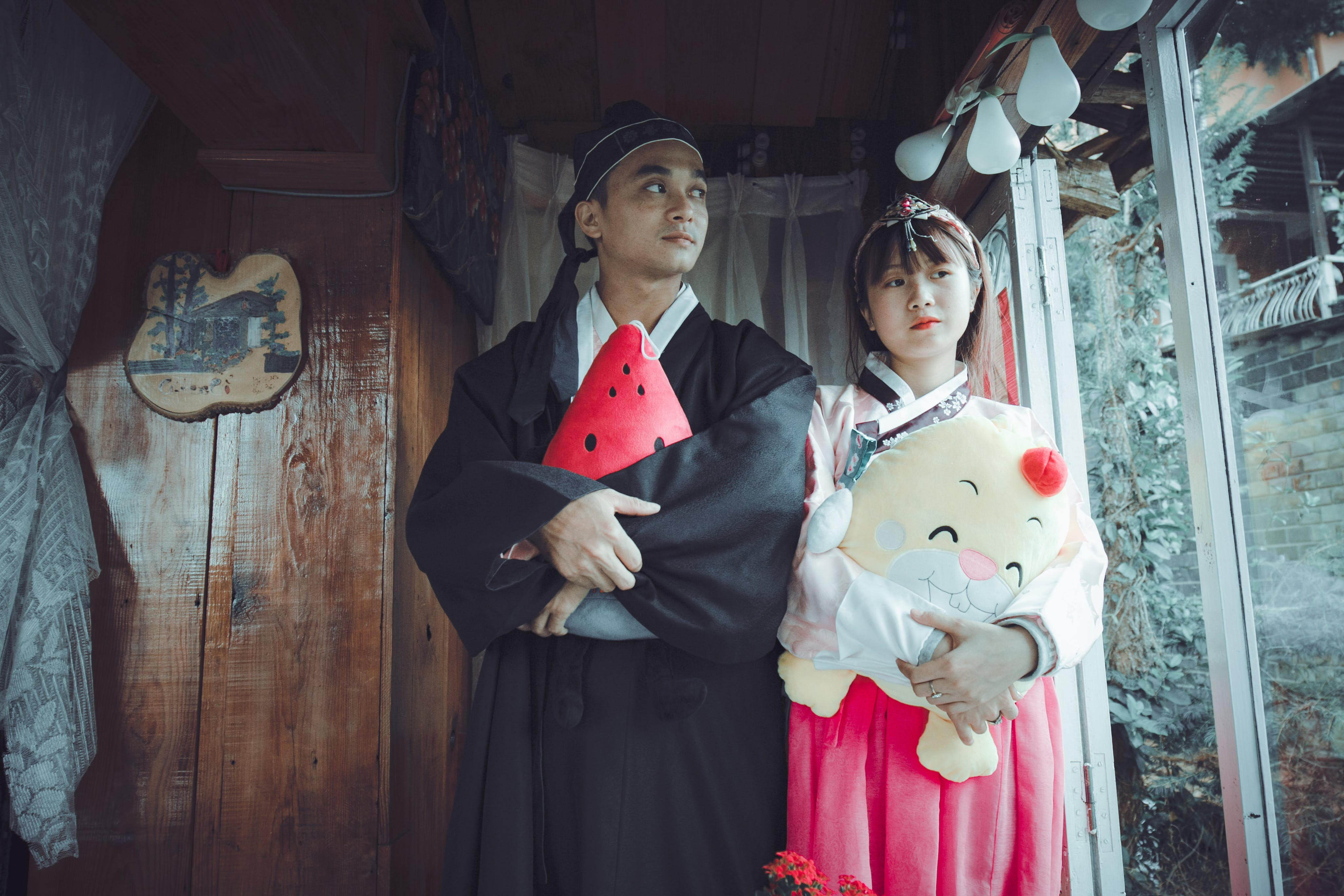 Man and Woman Holding Plush Toys Standing on Front of Brown Wall