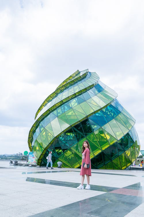 Woman in Red Dress Standing in Front of Green Glass Elliptical Building