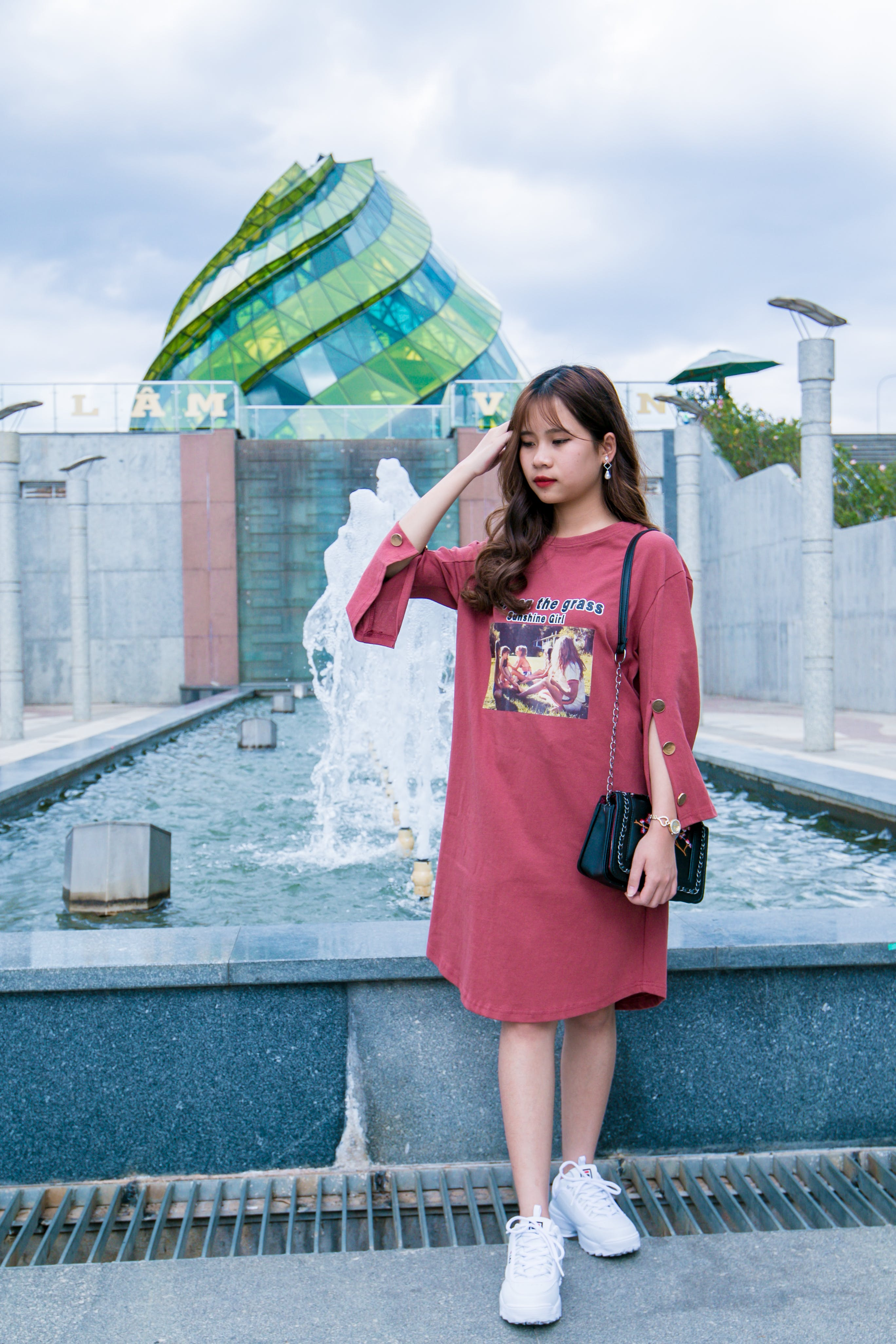 Woman Wearing Maroon Crew-neck Long-sleeved Dress Standing Next to Fountain Under Cloudy Sky