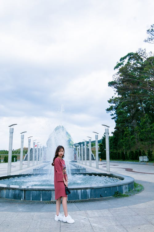 Woman in Red Long-sleeved Dress Standing Near Water Fountain at Daytime