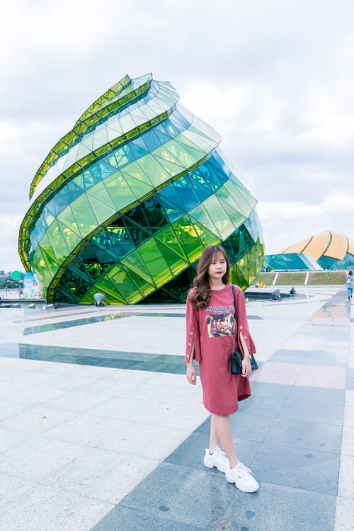 Woman in Red Long-sleeved Top Wearing White Sneakers Walking in Front of Green and Blue Glass Building