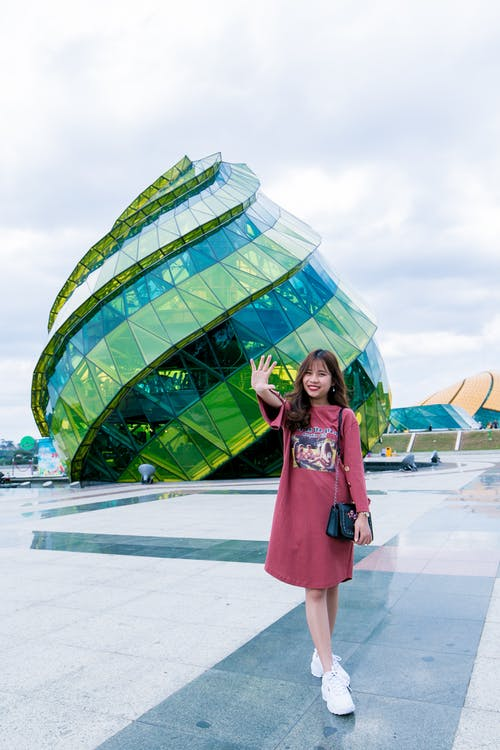Woman in Front of Green Glass Building