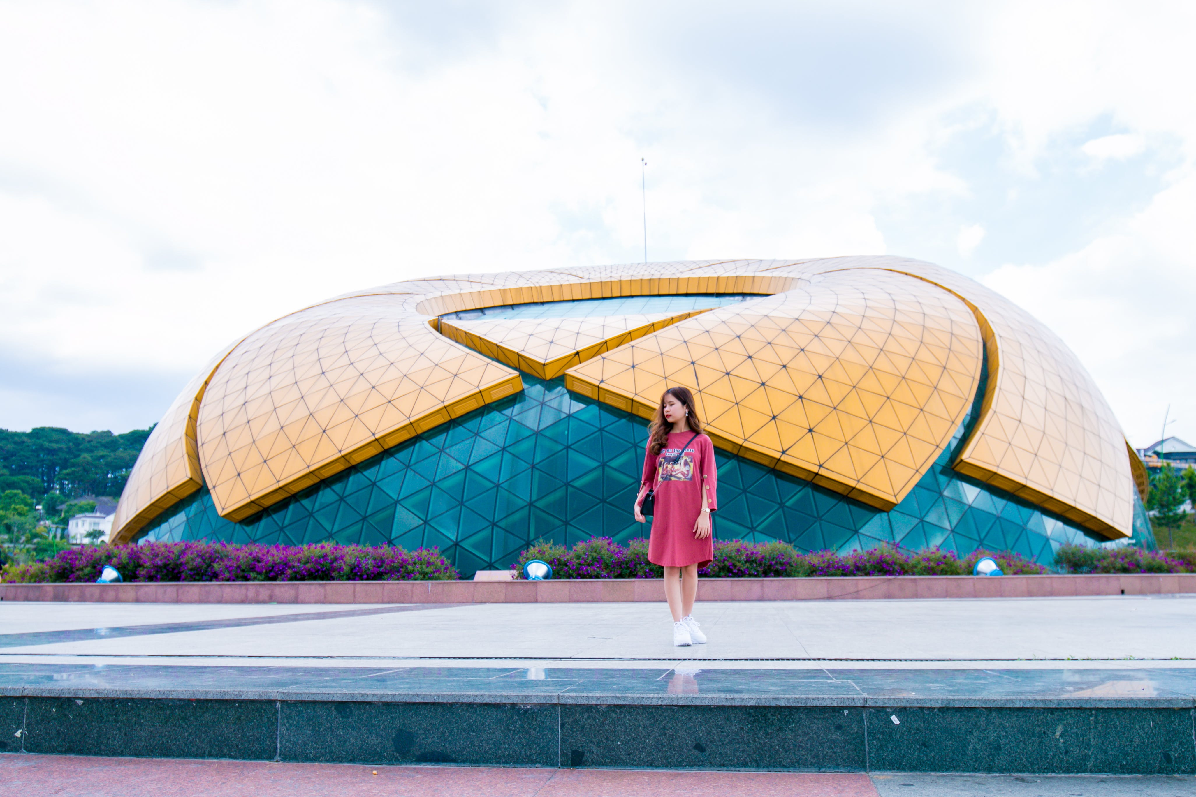 Woman Standing Near Blue and Yellow Dome Under White Cloudy Skies at Daytime