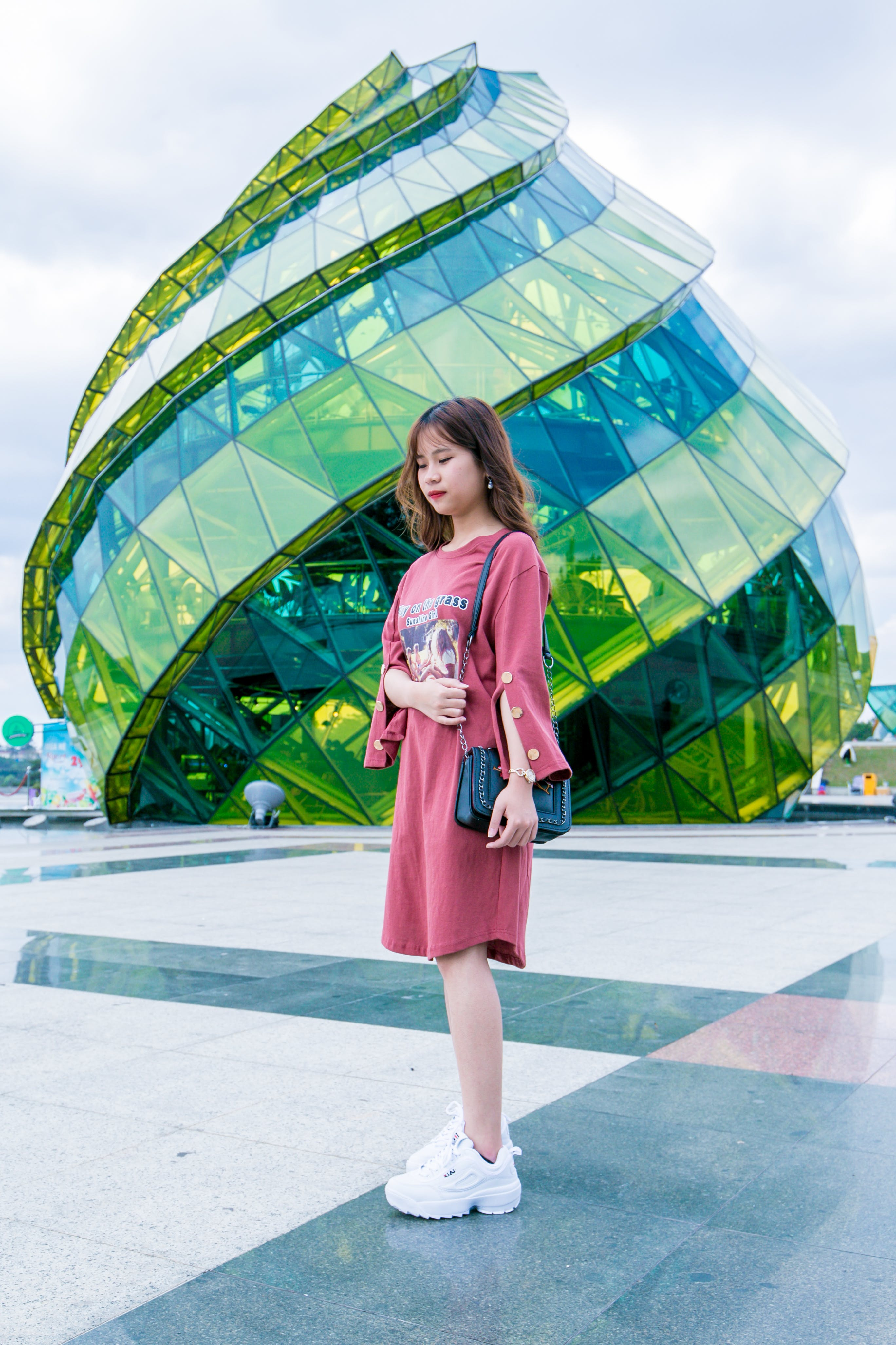 Girl Wearing Red Long-sleeved Dress and White Low-top Shoes Standing Near Green Glass Structure