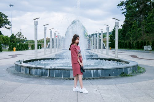 Woman Wearing Pink Crew-neck Long-sleeved Midi Dress Standing Concrete Outdoor Fountain