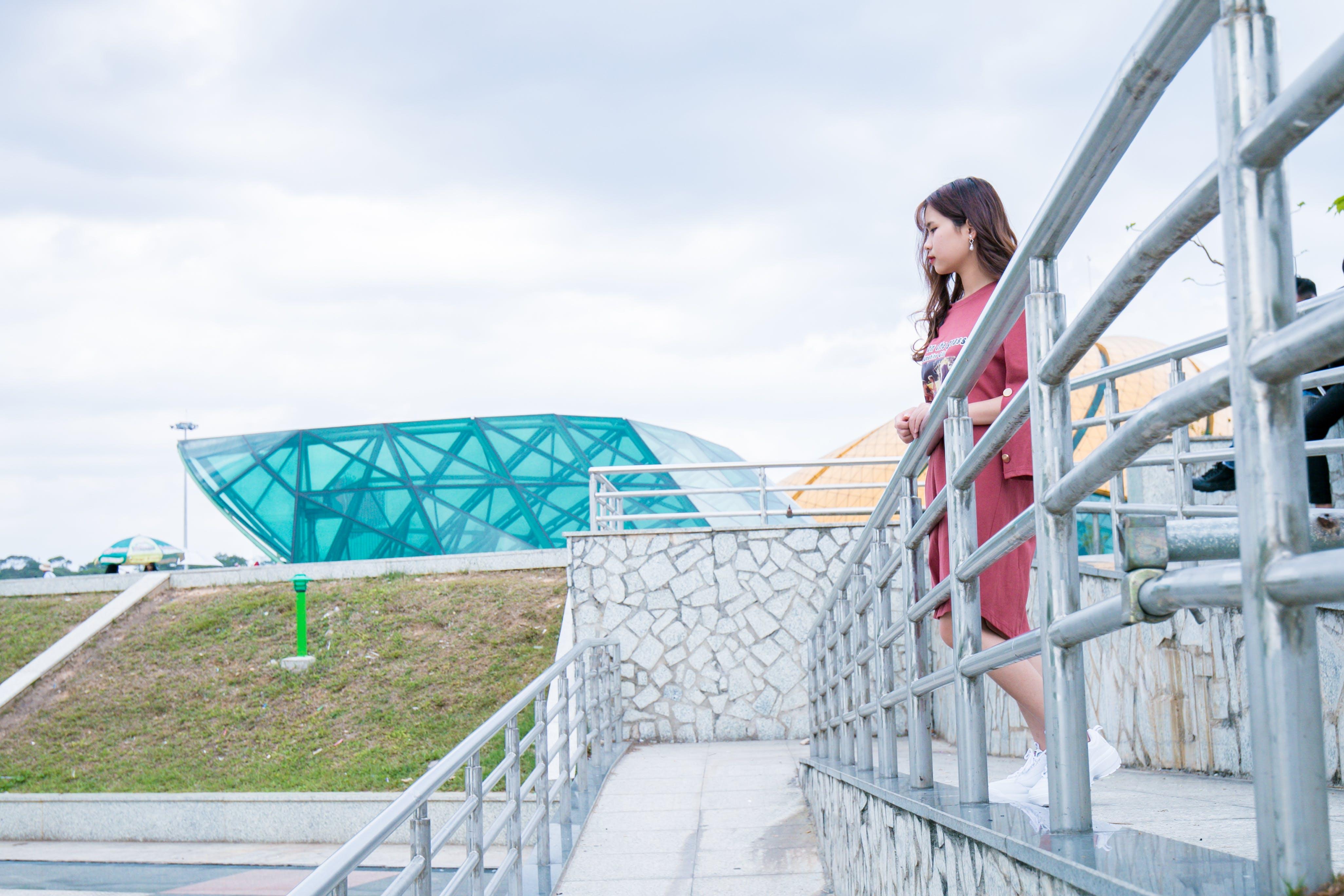 Woman Wearing Red Crew-neck Dress Near Gray Wall