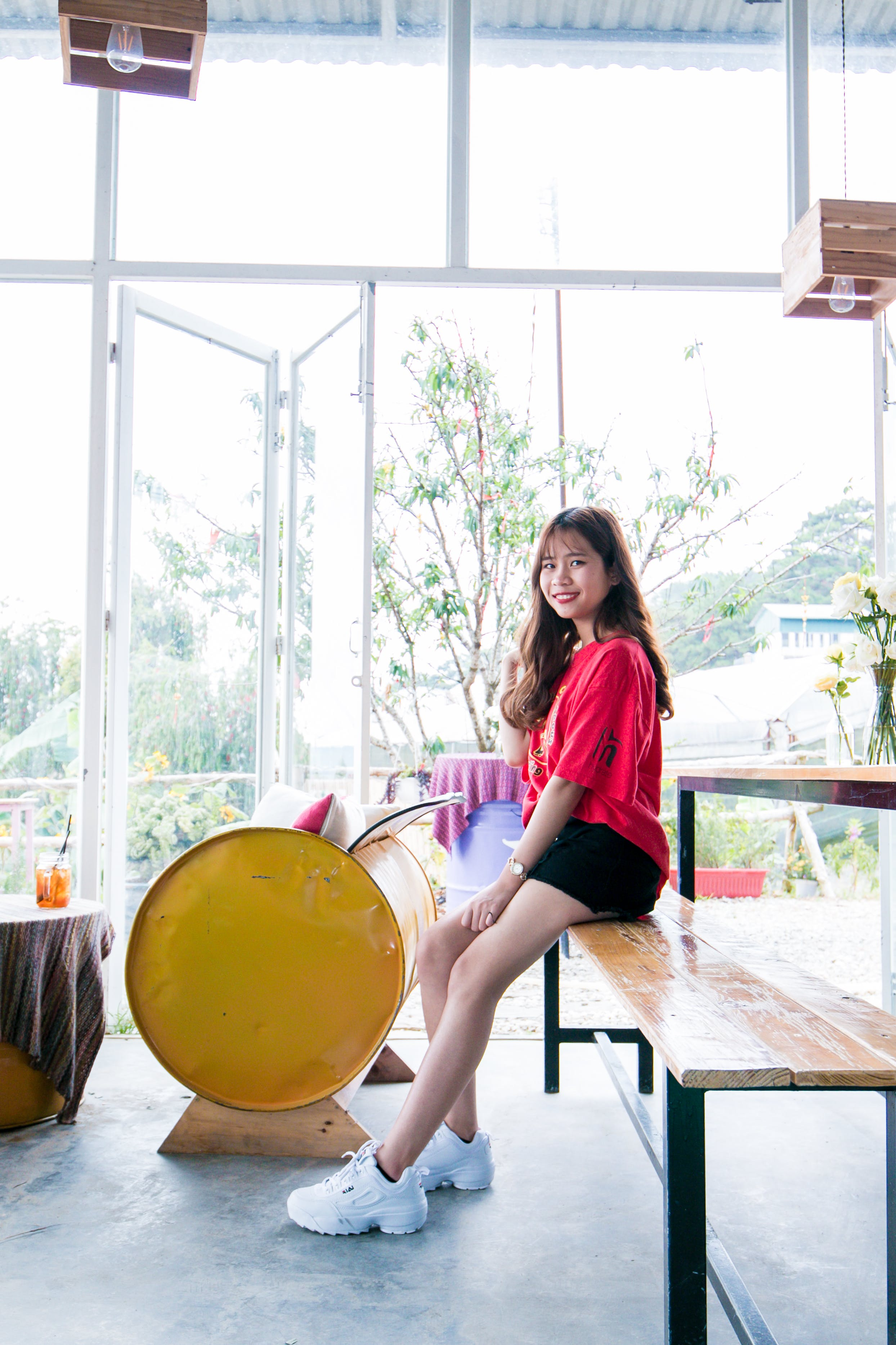 Woman Wearing Red Blouse and Black Short While Sitting on Table