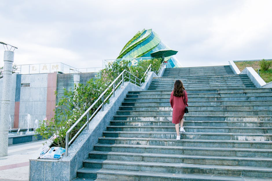 Woman Wearing Red Dress on Gray Stairs