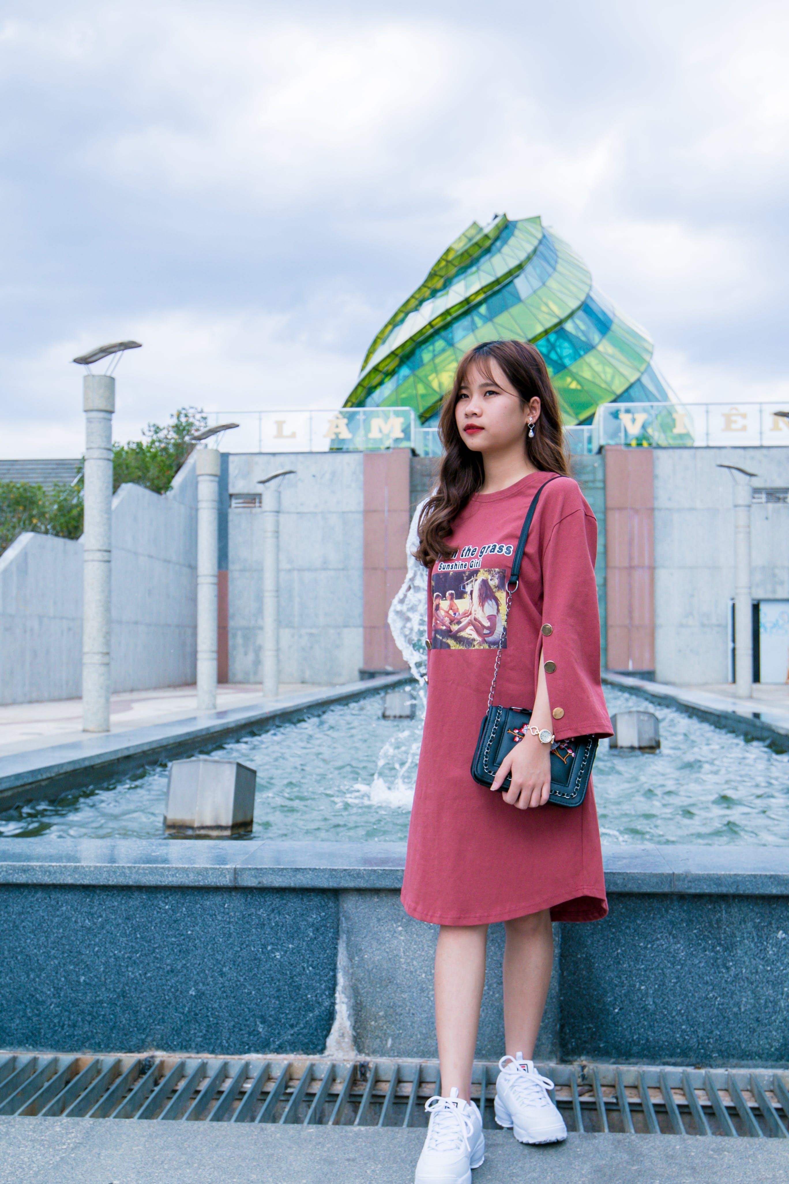 Woman Wearing Red Dress Standing Near Fountain