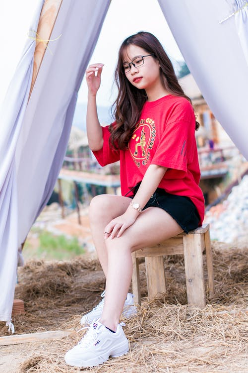 Woman Wearing Red Crew-neck Elbow-sleeved Shirt Sitting on Brown Wooden Stool