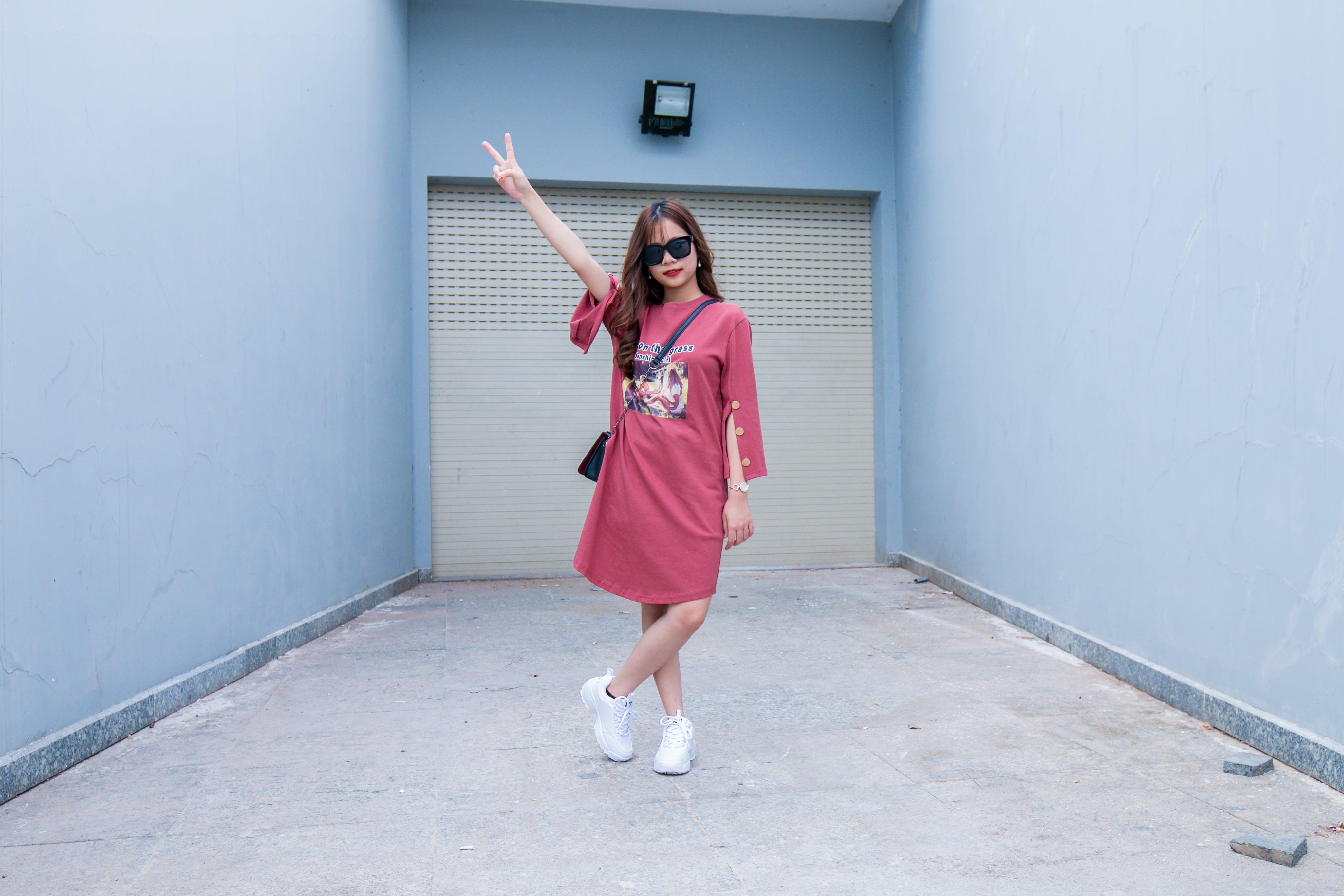 Woman Wearing Red Long-sleeved Dress Standing in Front of Shutter Door