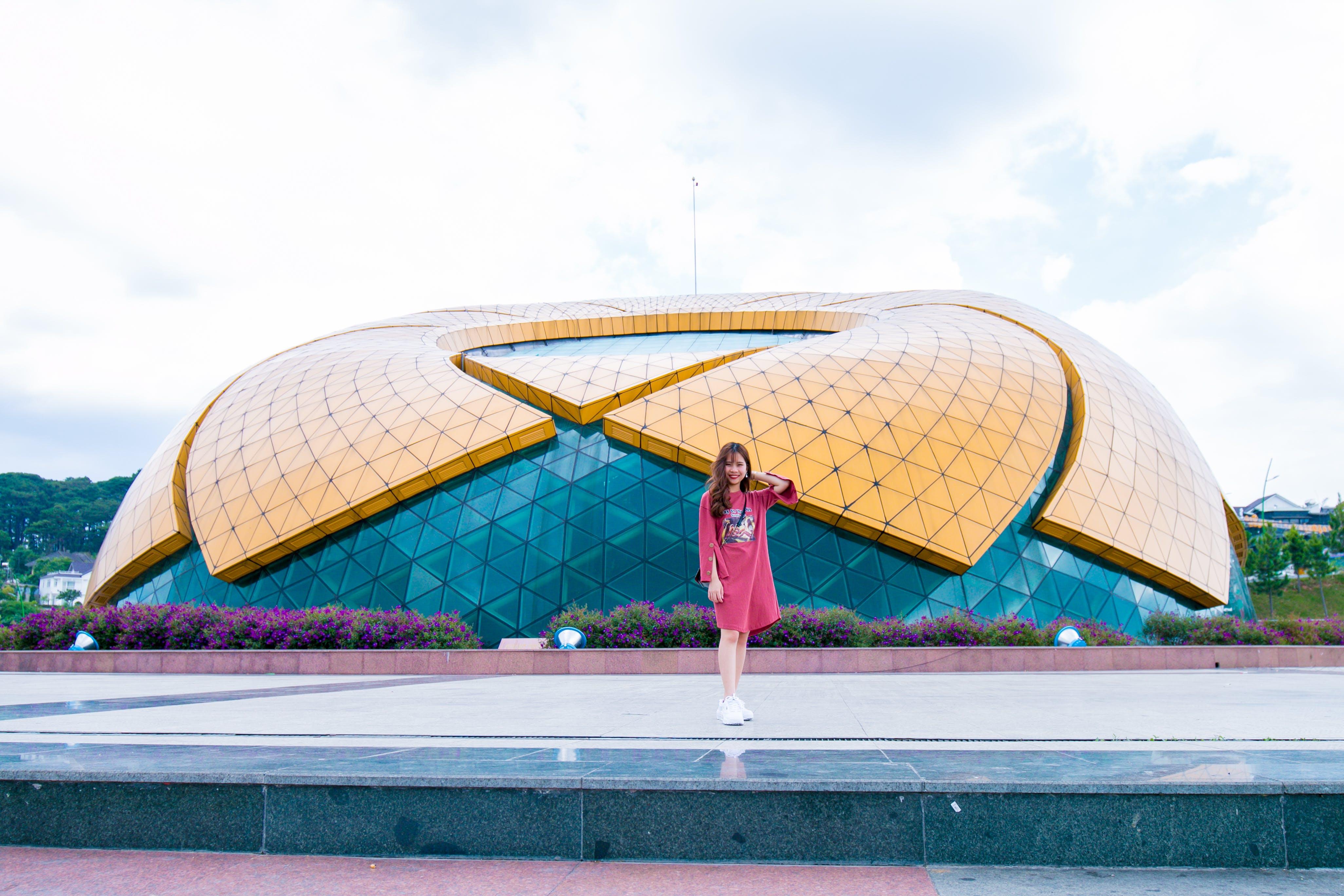 Woman in Red Dress Standing Near Stadium
